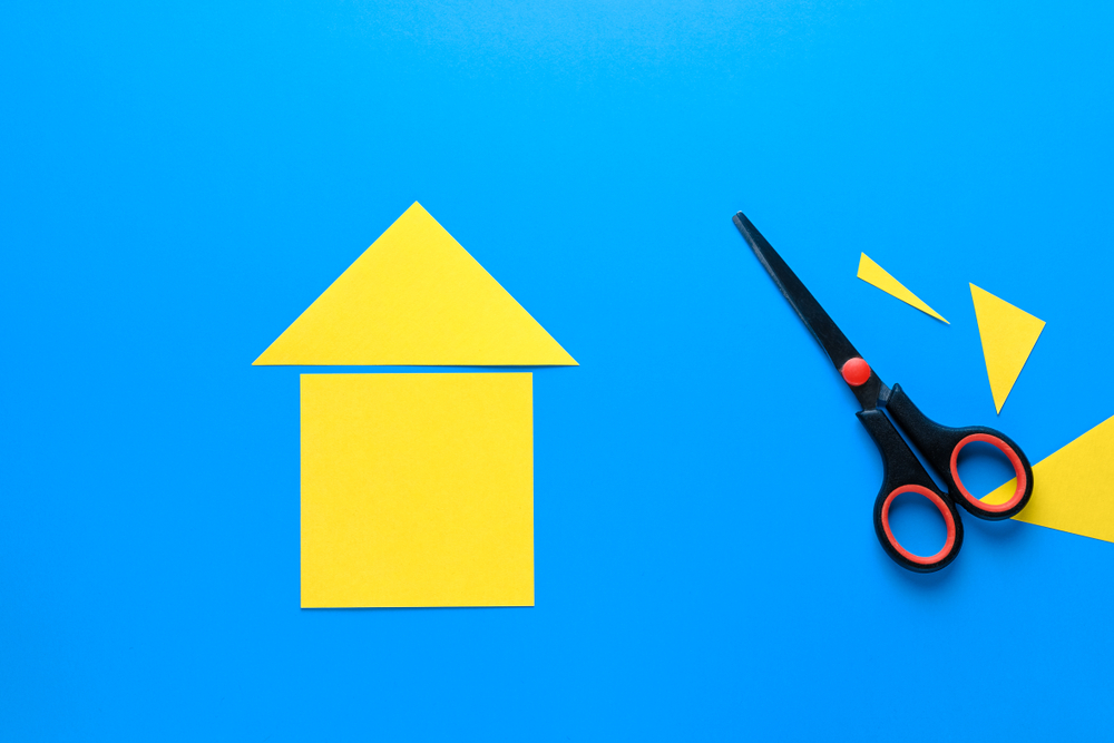 A house cut out of yellow paper. There Are Scissors Nearby.