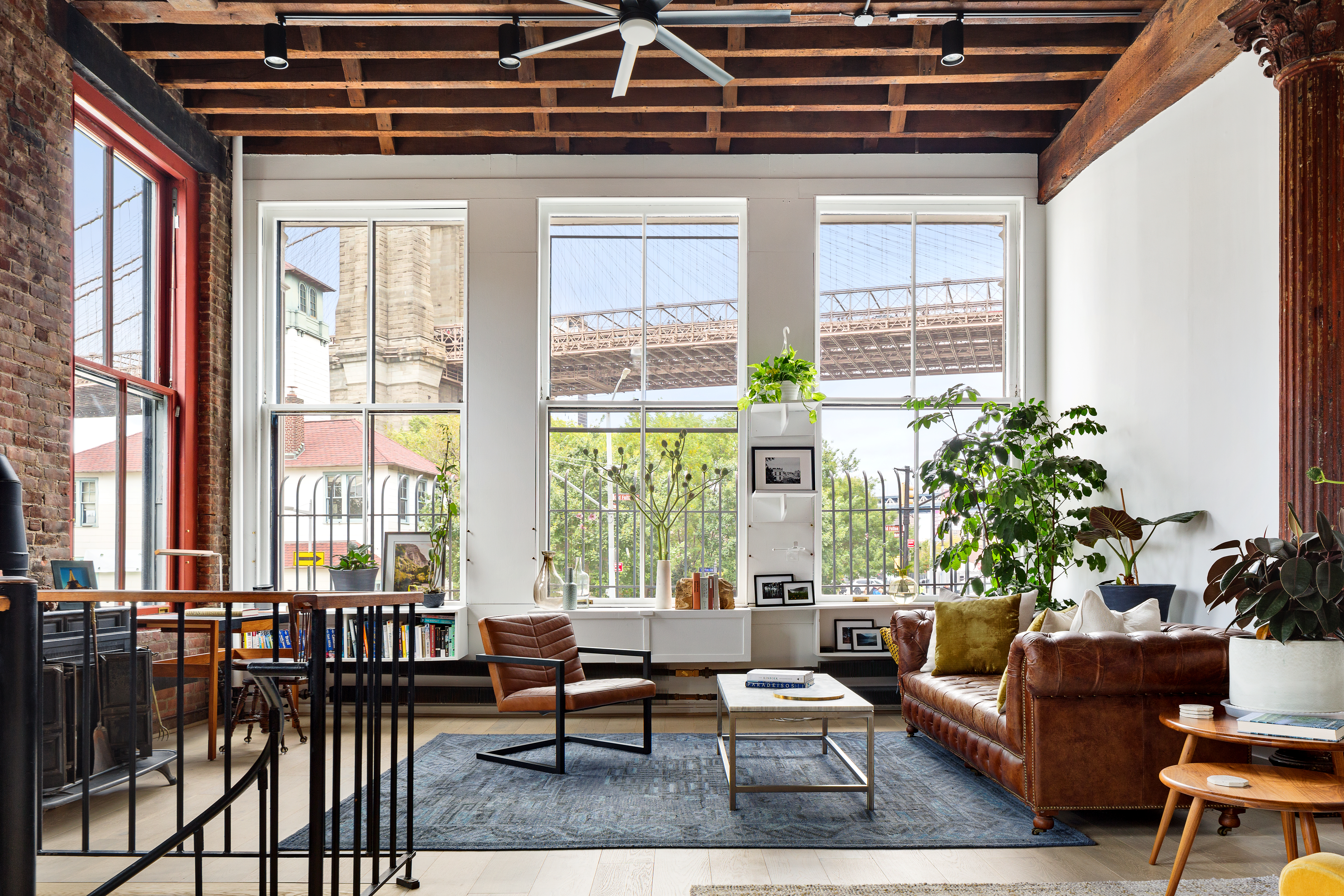 A living room with large windows, a brown leather couch, and a rug.