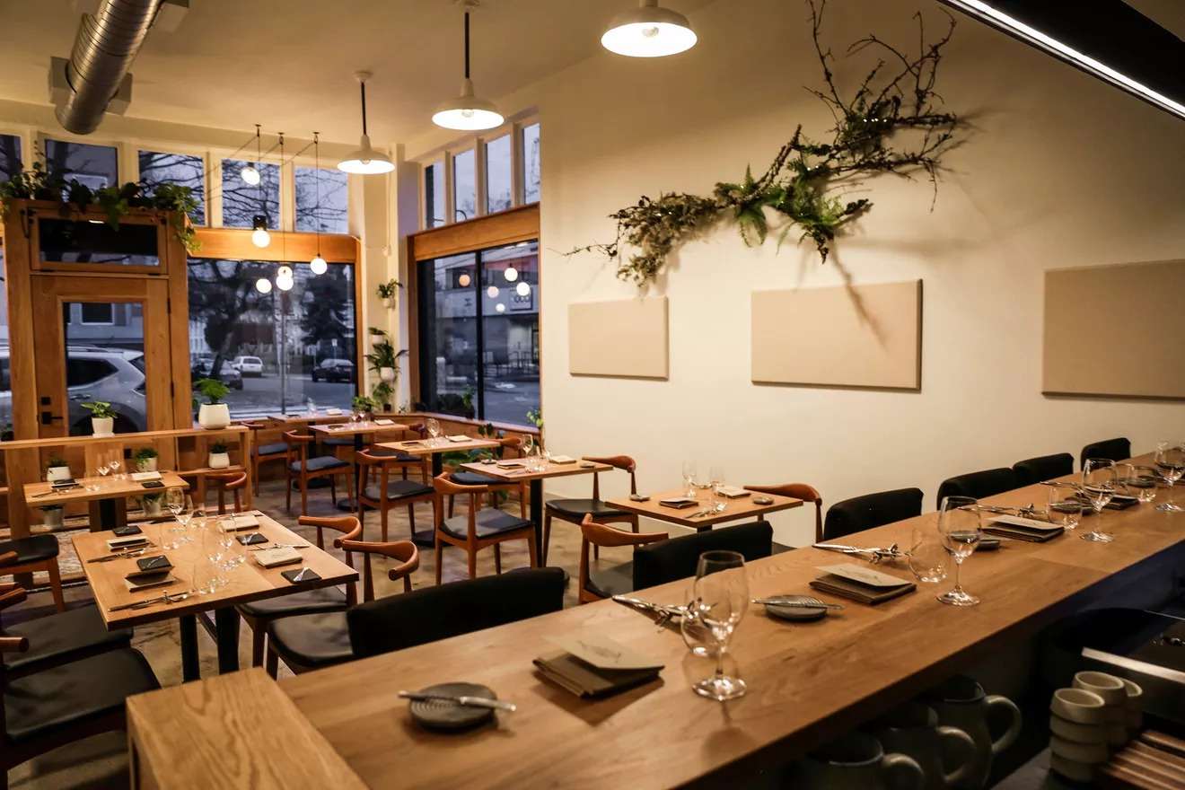 The dining room of Farm Spirit has several small wooden tables with wishbone chairs, a wooden chef's counter looking into the kitchen, and living plant installations