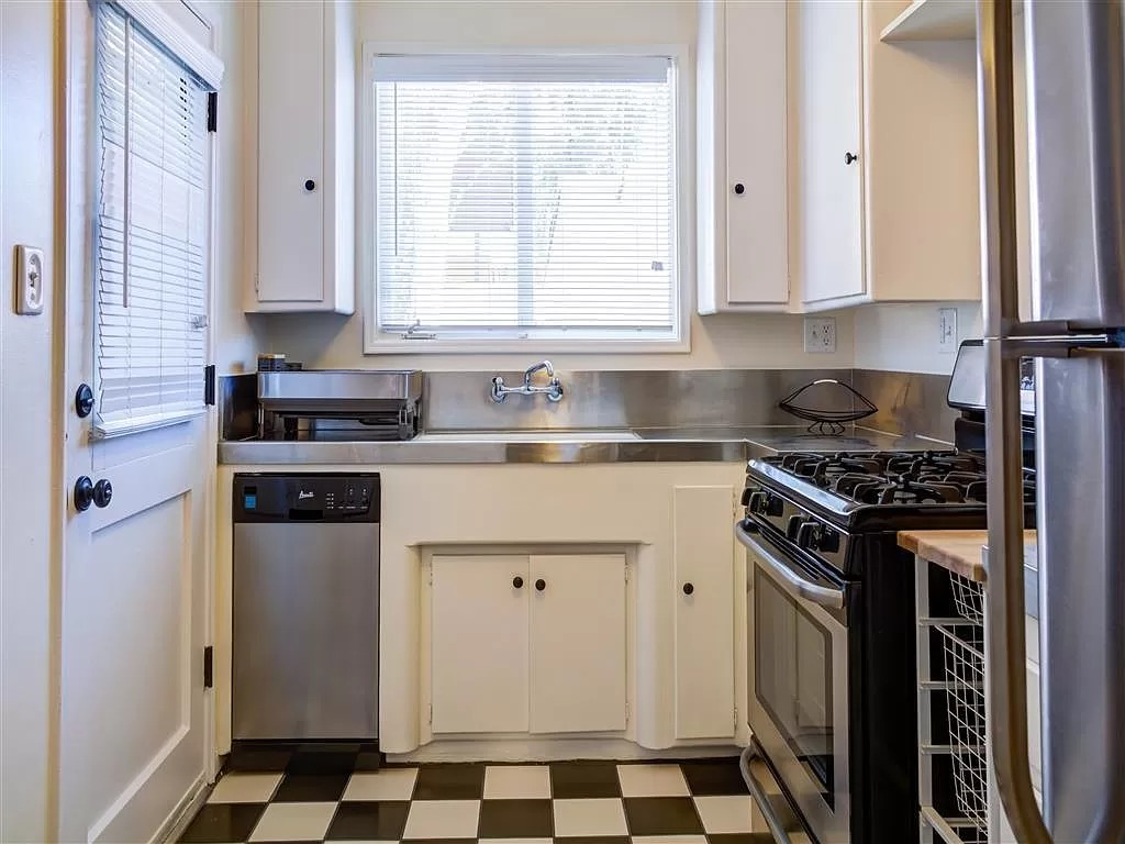 A small kitchen with stainless steel appliances and a checkerboard floor