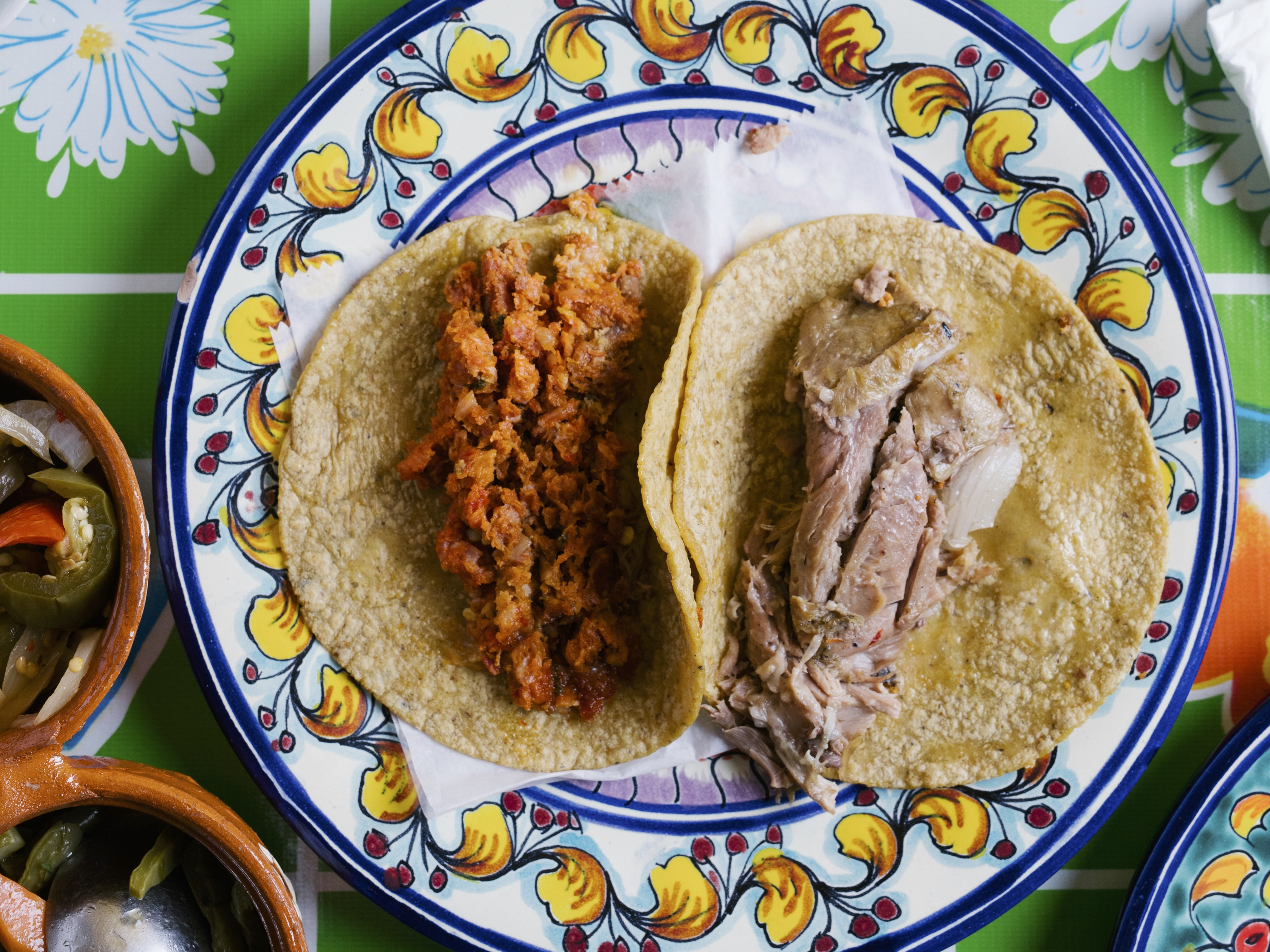 An overhead photograph of two corn tortillas, one filled with crumbly orange meat and another with brown- and pink-colored meat slices.
