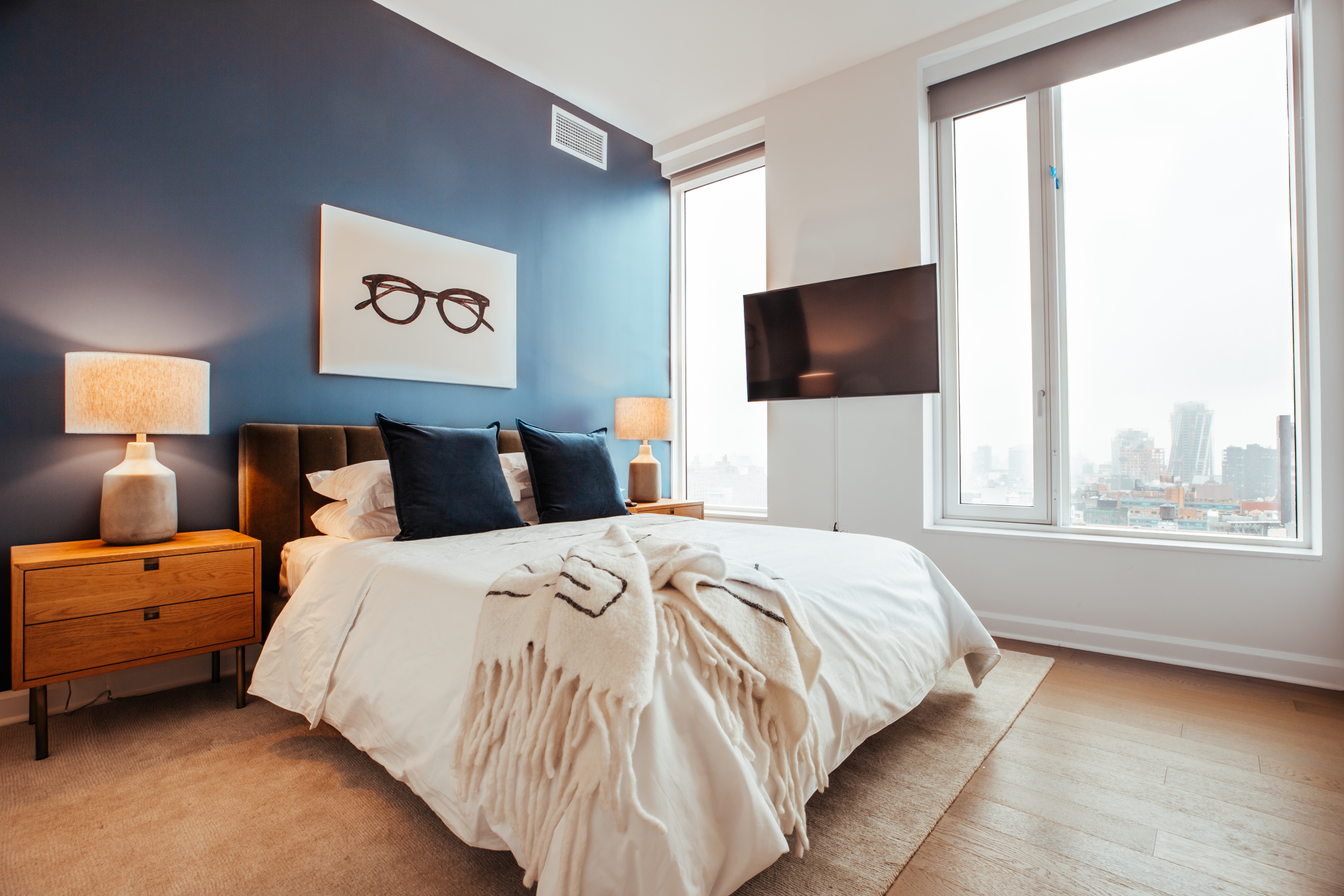 A furnished apartment in New York City, featuring a blue wall, white bedspread, and eyeglass poster above the headboard.
