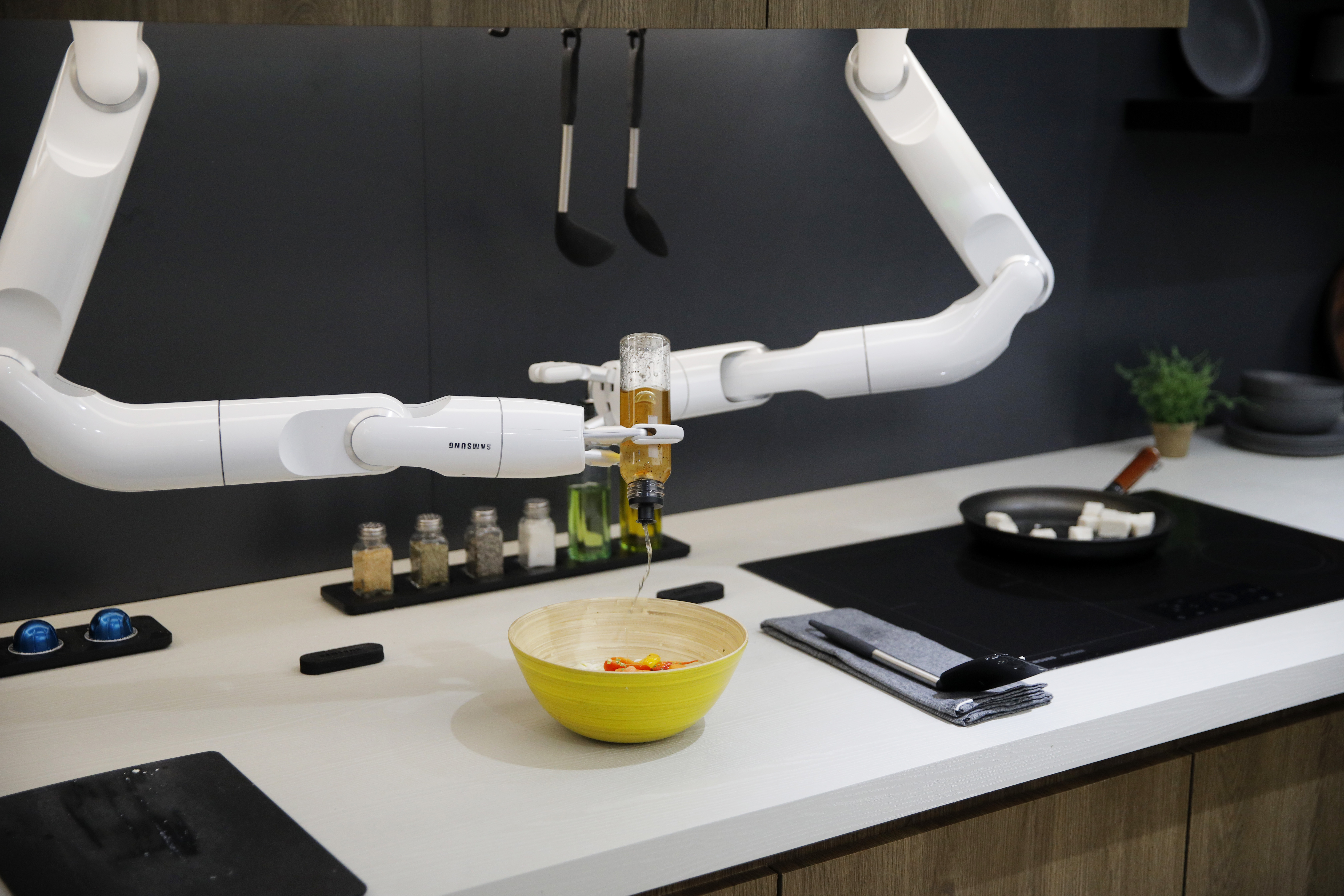 The Bot Chef pours dressing into a salad during a demonstration at the Samsung booth during the CES tech show, Tuesday, Jan. 7, 2020, in Las Vegas. The robot is designed to help with cooking tasks, not to make a meal all on it's own