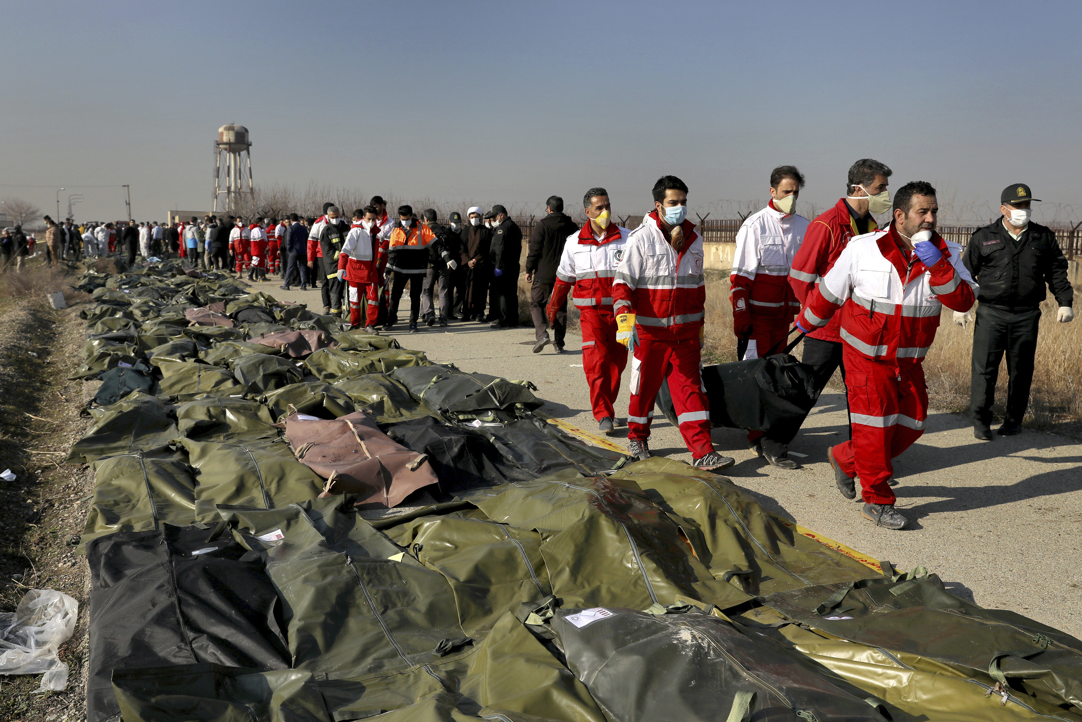 Rescue workers carry the body of a victim of a Ukrainian plane crash in Shahedshahr, southwest of the capital Tehran, Iran, on Wednesday, Jan. 8, 2020. A Ukrainian passenger jet carrying 176 people crashed on Wednesday, just minutes after taking off from the Iranian capital's main airport, turning farmland on the outskirts of Tehran into fields of flaming debris and killing all on board. (AP Photo/Ebrahim Noroozi) ORG XMIT: ENO101