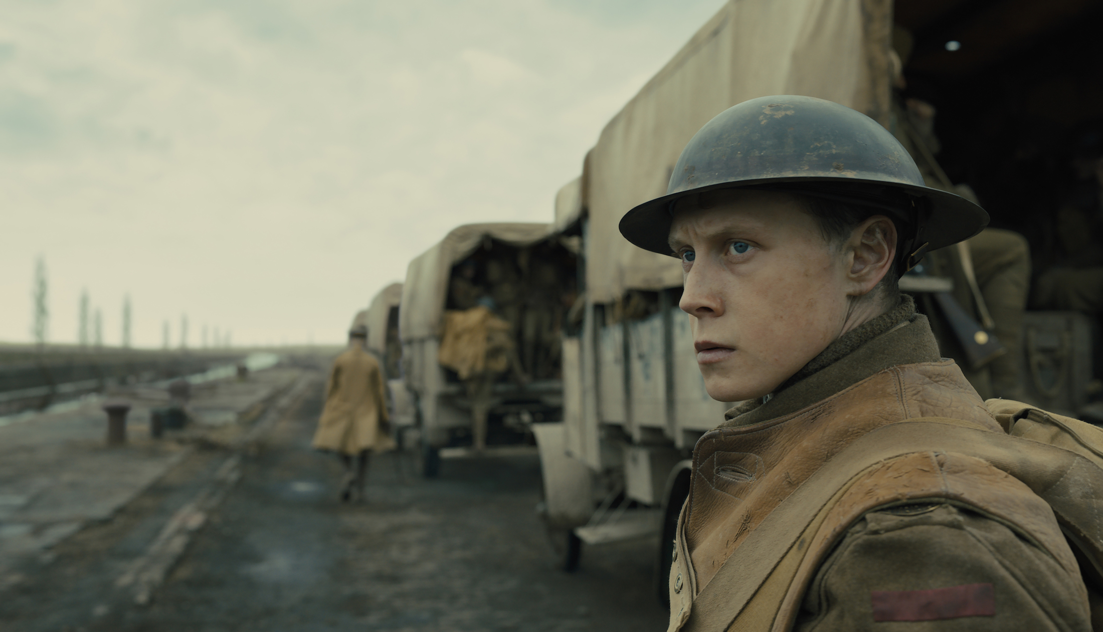 George MacKay as Schofield, looking away from a line of WWI trucks driving down a dirt road in 1917