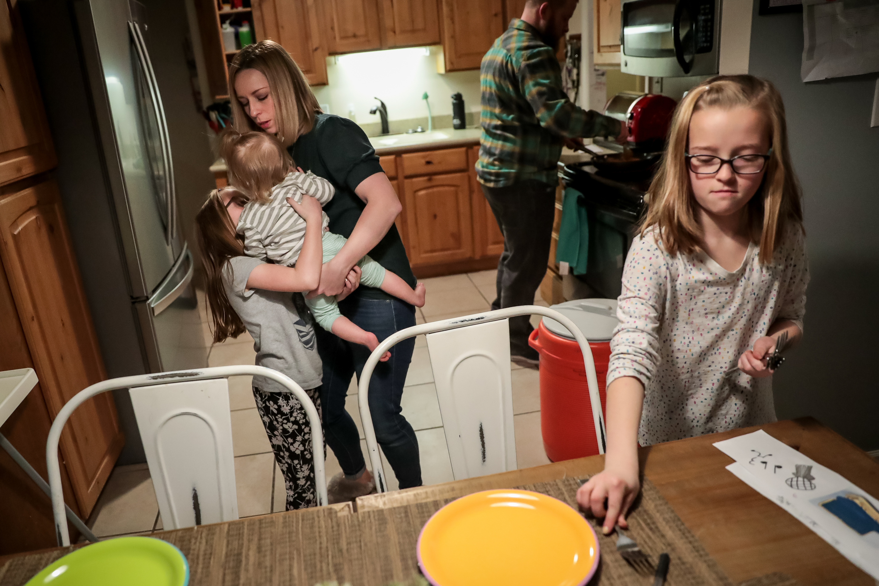 Cindy Maudsley passes Ivy, 11 months, to Phoebe, 8, while Lyla, 10, sets the table and AJ Maudsley, background, cooks dinner at their home in Bountiful on Tuesday, Jan. 7, 2020.