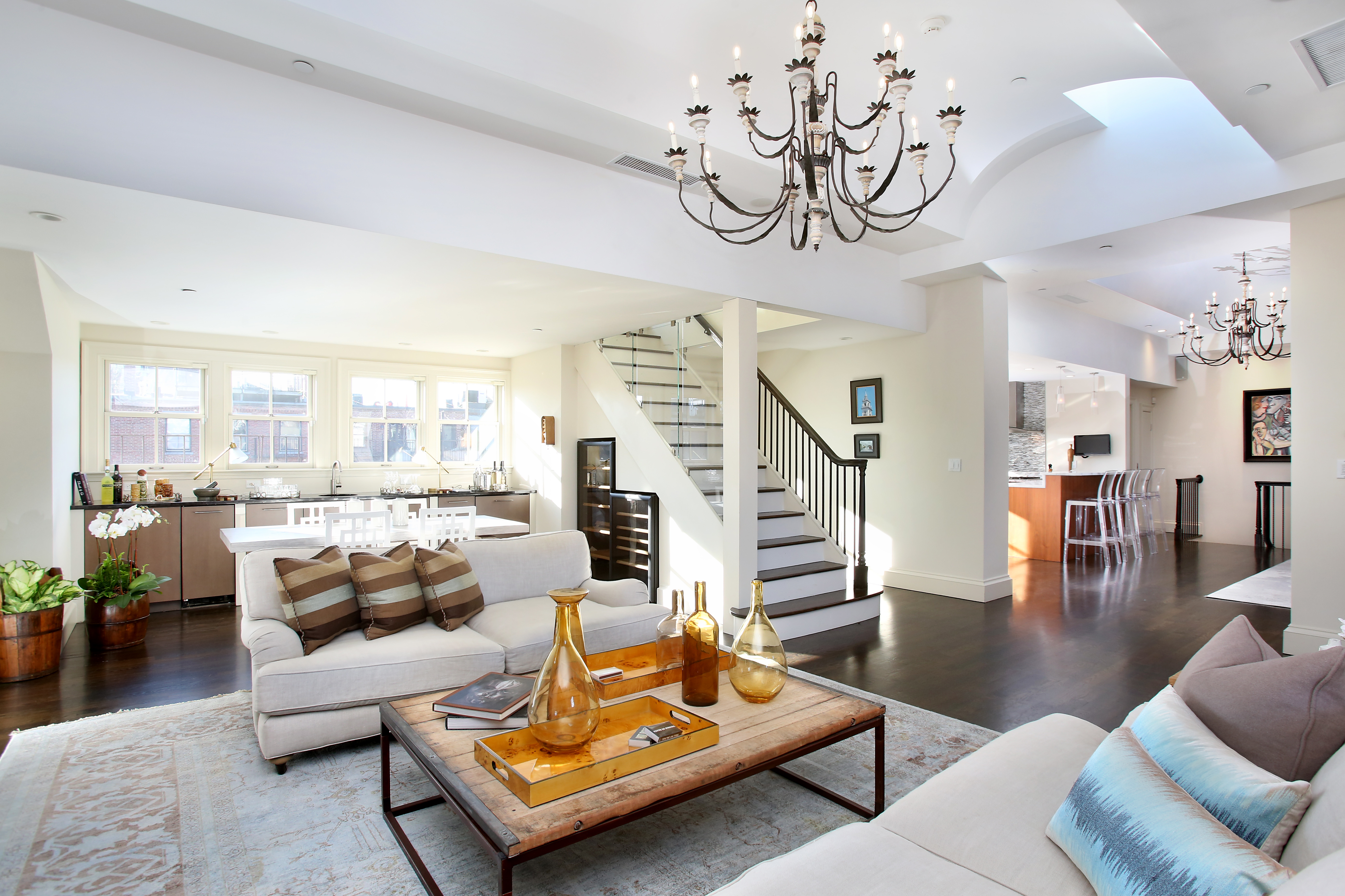 A spacious living room with furniture and a staircase leading into it.