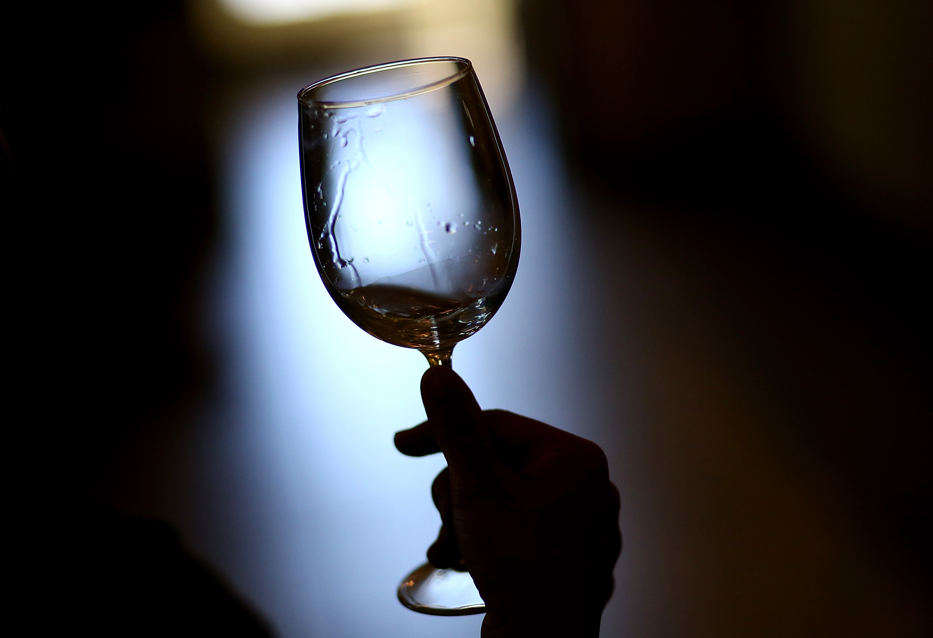 A hand holding a wine glass up to the light.