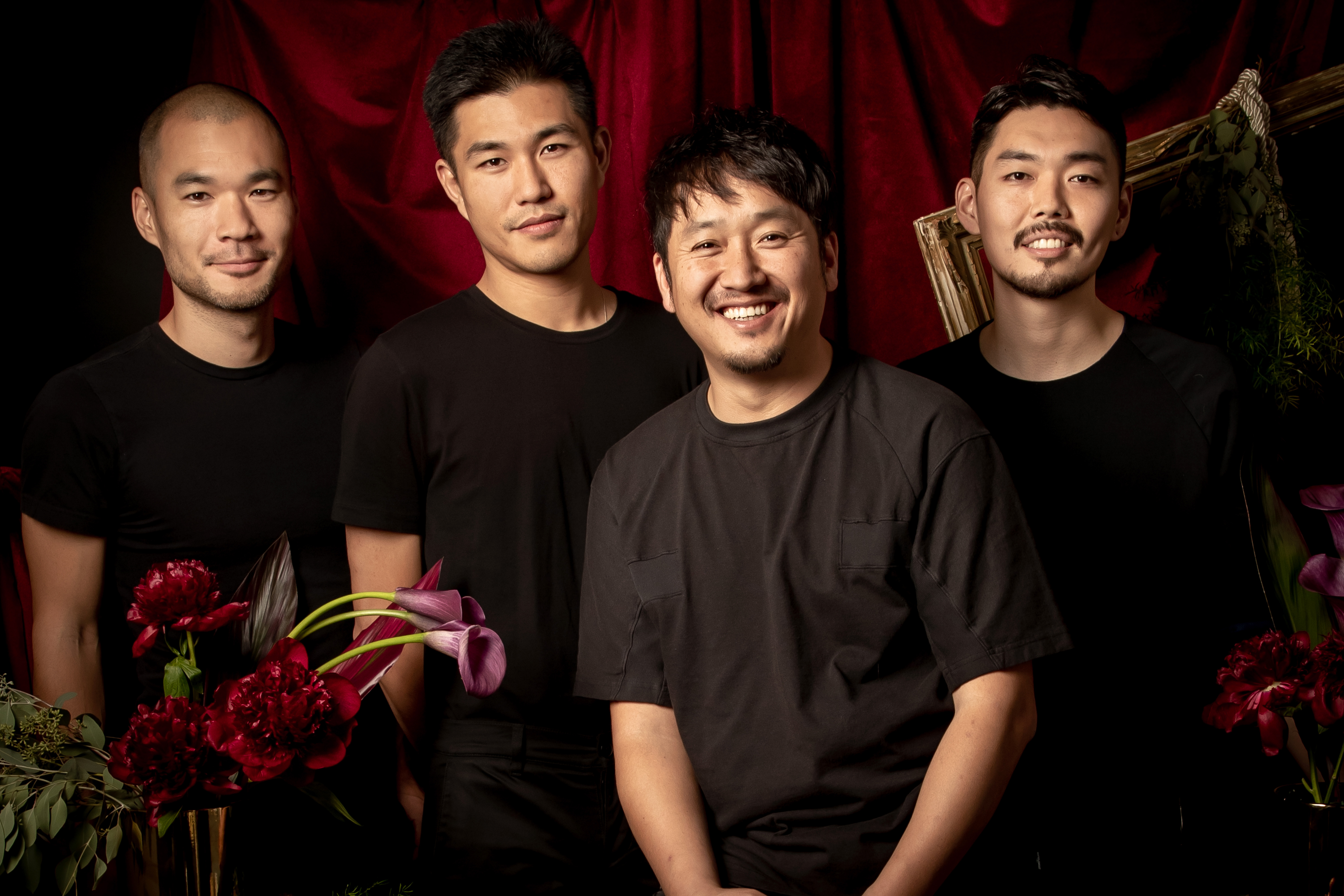 Four men pose in front of a velvet red curtain. To the left and right of the group there are red flowers.
