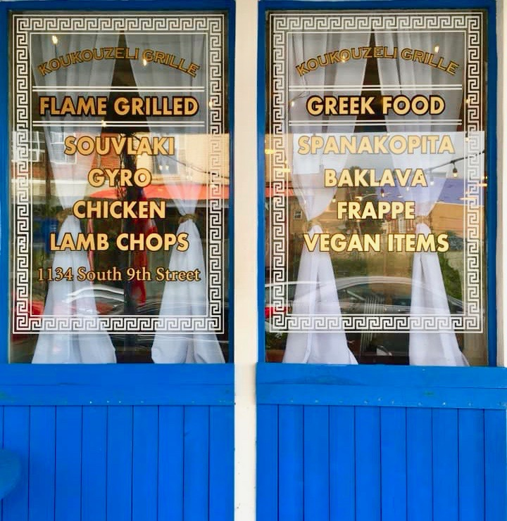 blue and white store front with greek foods listed on window