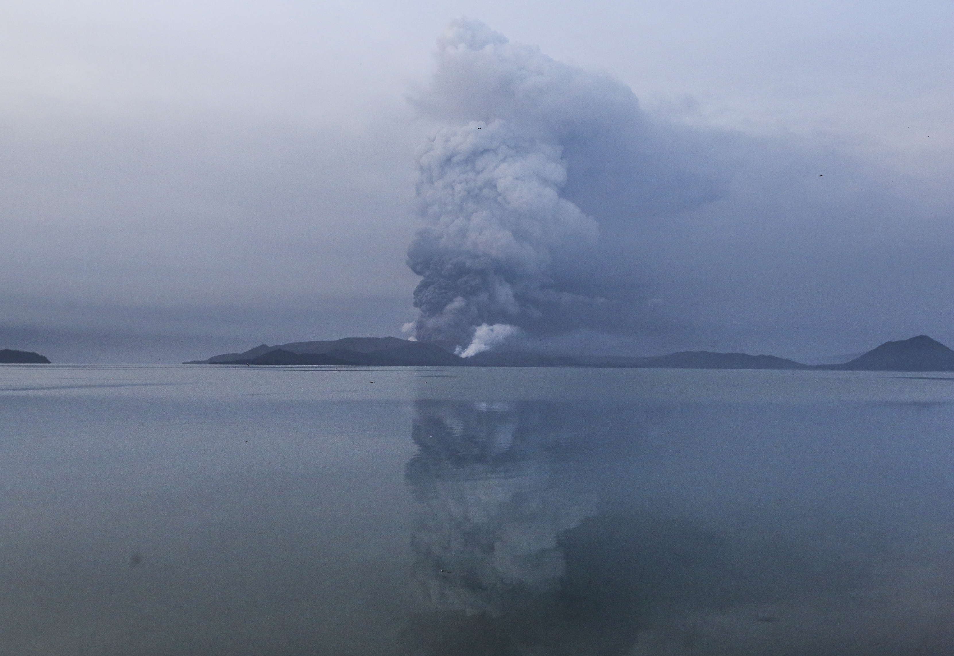 Taal volcano spews ash in view from Batangas, southern Philippines on Monday, Jan. 13, 2020. Red-hot lava gushed out hereof a volcano near the Philippine capital on Monday, as thousands of people fled the area through heavy ash. Experts warned that the eruption could get worse and plans were being made to evacuate hundreds of thousands. (AP Photo/Gerrard Carreon)