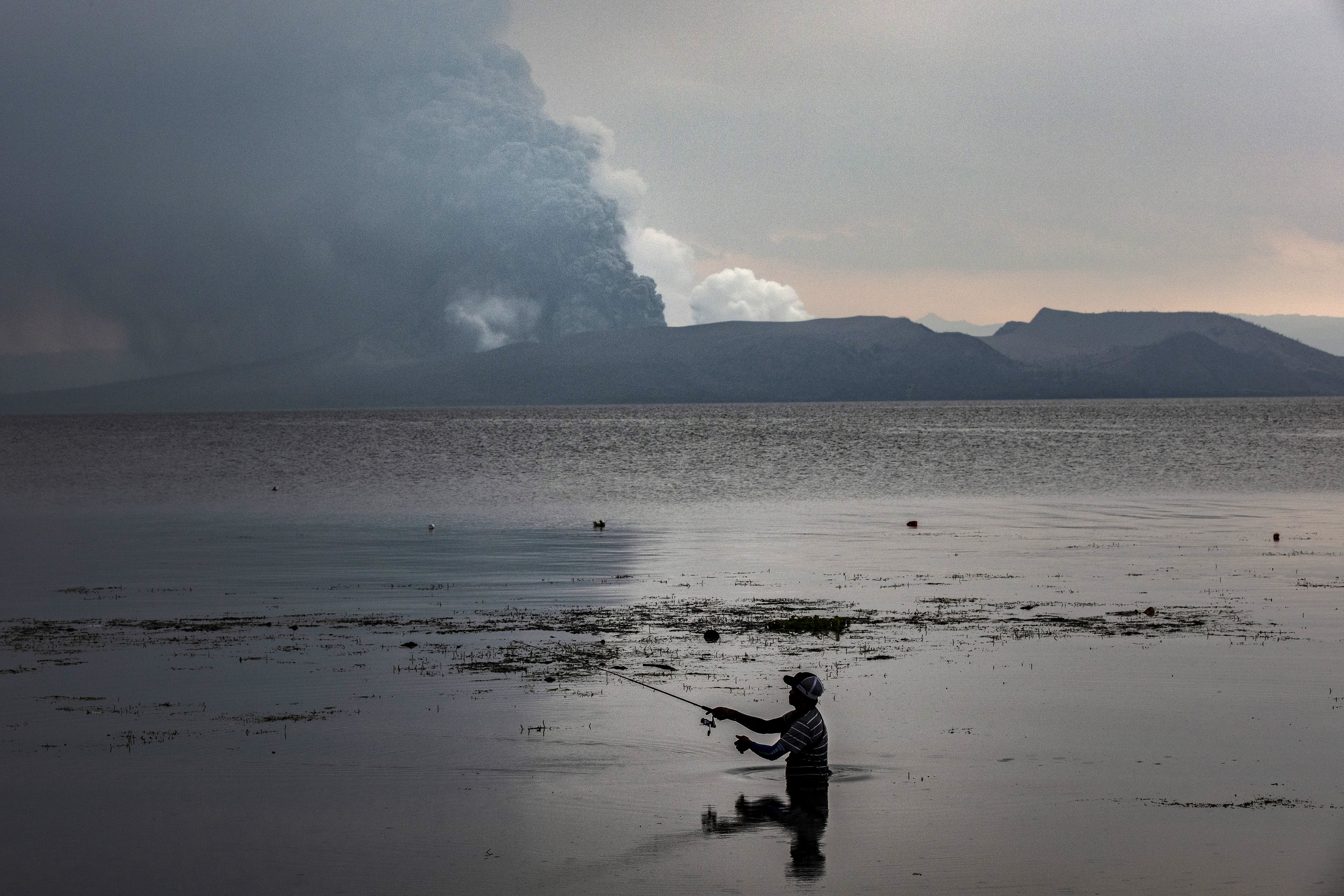 A resident fishes at a lake as Taal Volcano erupts on January 13, 2020 in Balete, Batangas province, Philippines.
