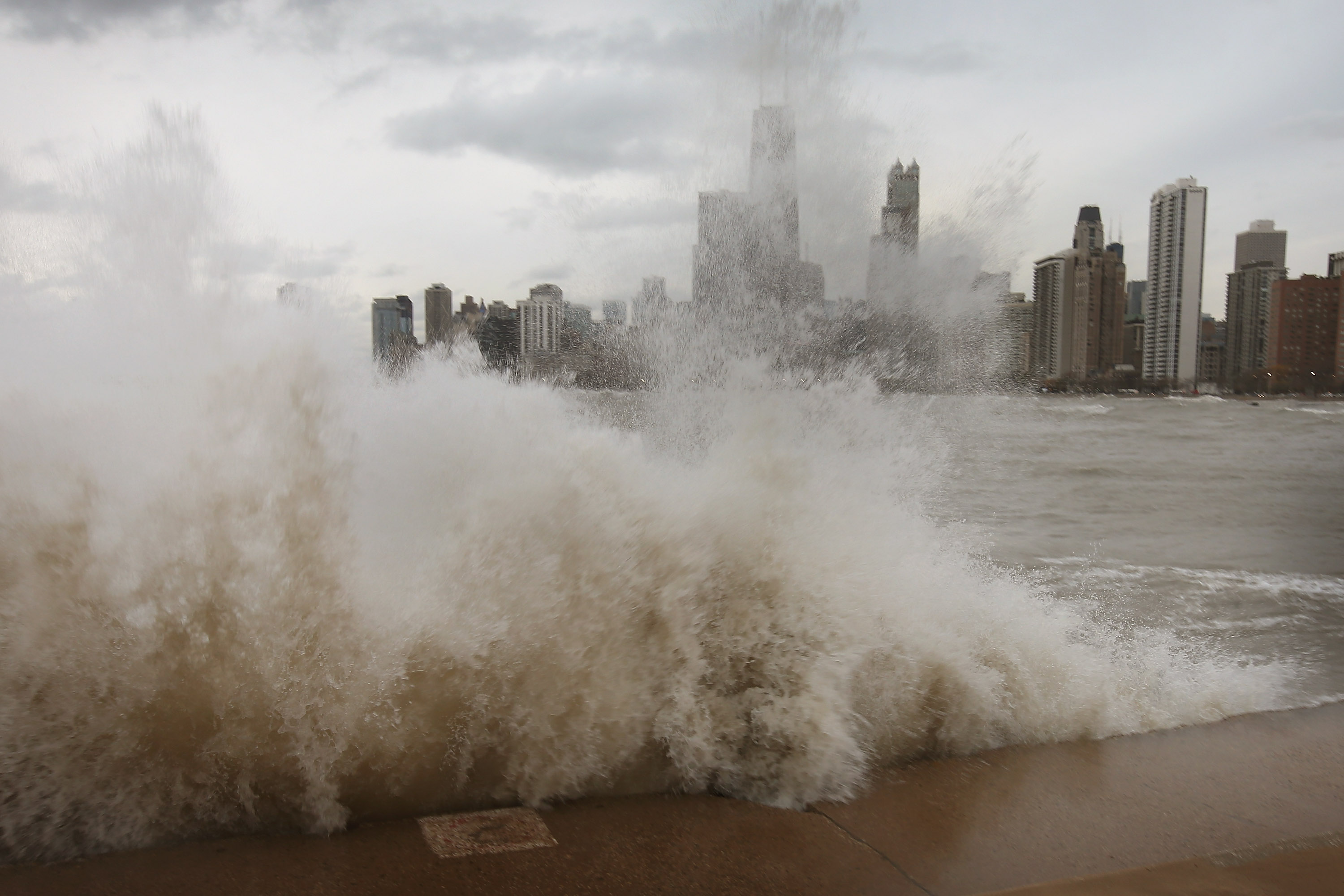 A large wave crashes along the lakefront trail. There are tall buildings in the distance.