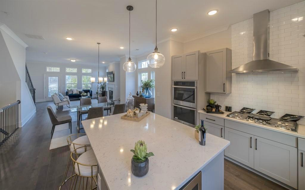 A white kitchen with a large island and big pendants.