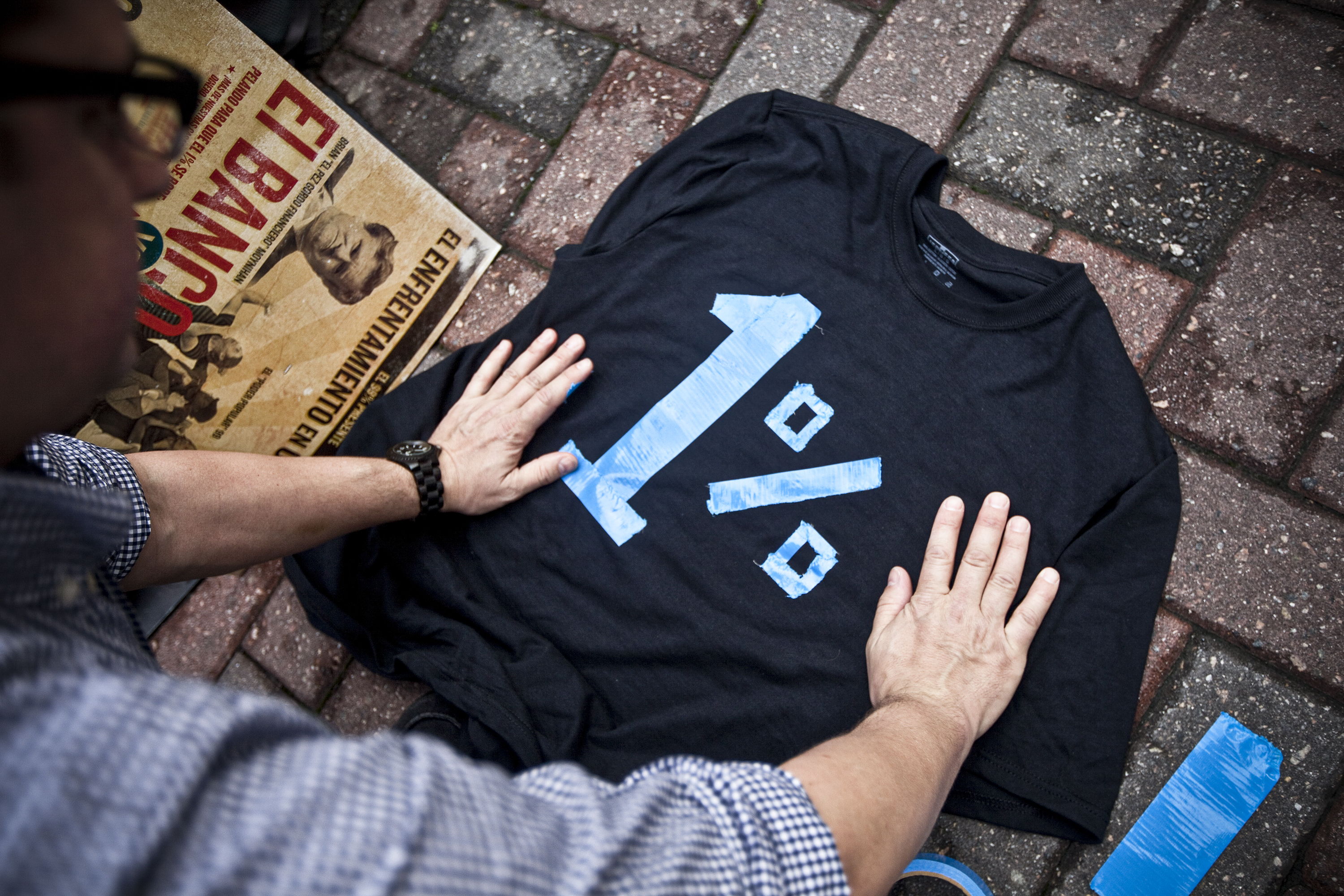 "An Occupy Wall Street protester makes a black shirt that reads: ""1 percent."""