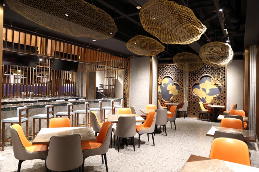 A large Chinese-style dining room space with orange chairs and wooden tables.