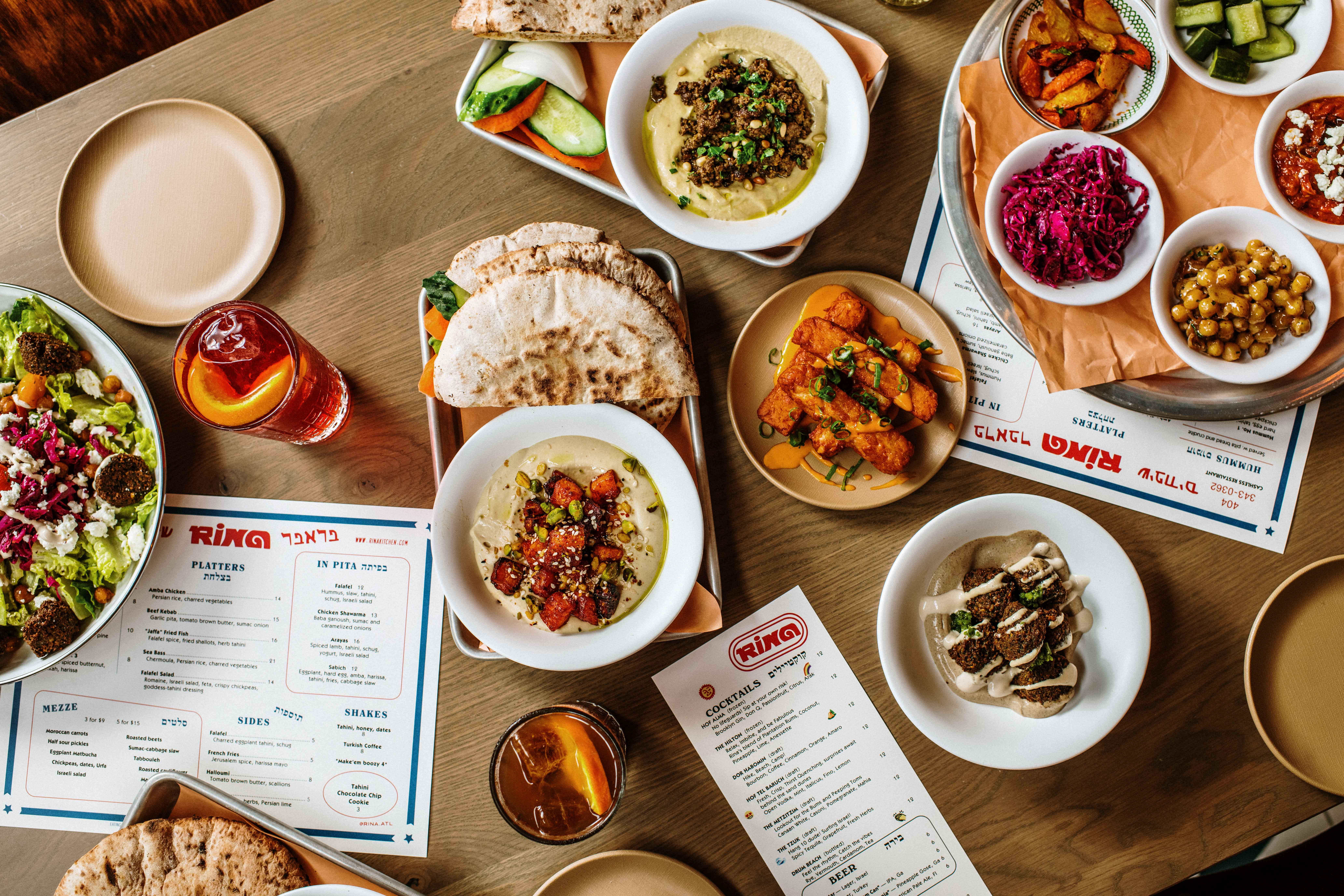 A large mezze and hummus spread on a table at Rina on the Beltline