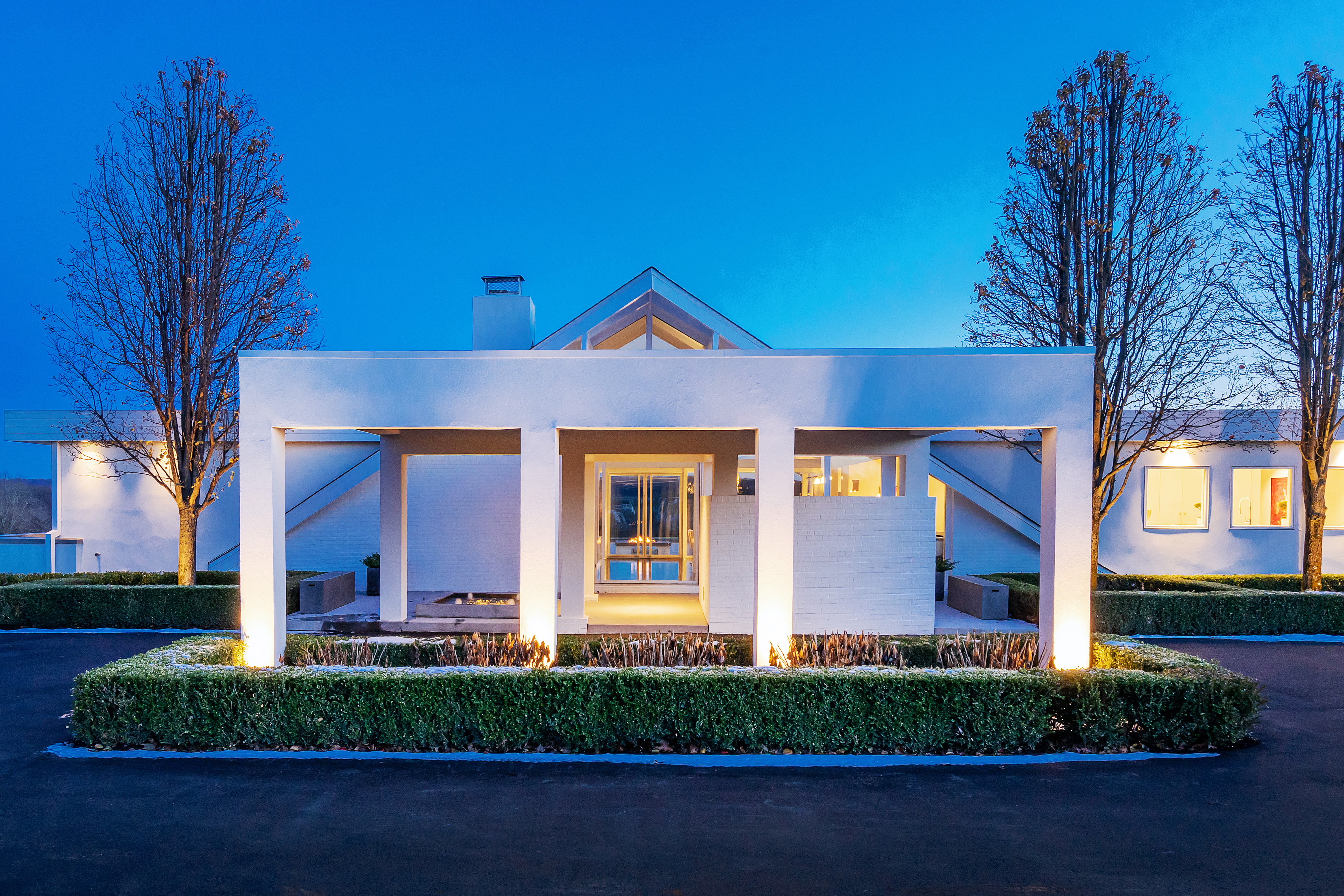 A night view of a white house that features a boxy entrance and an A-Frame-style peaked roof behind it.