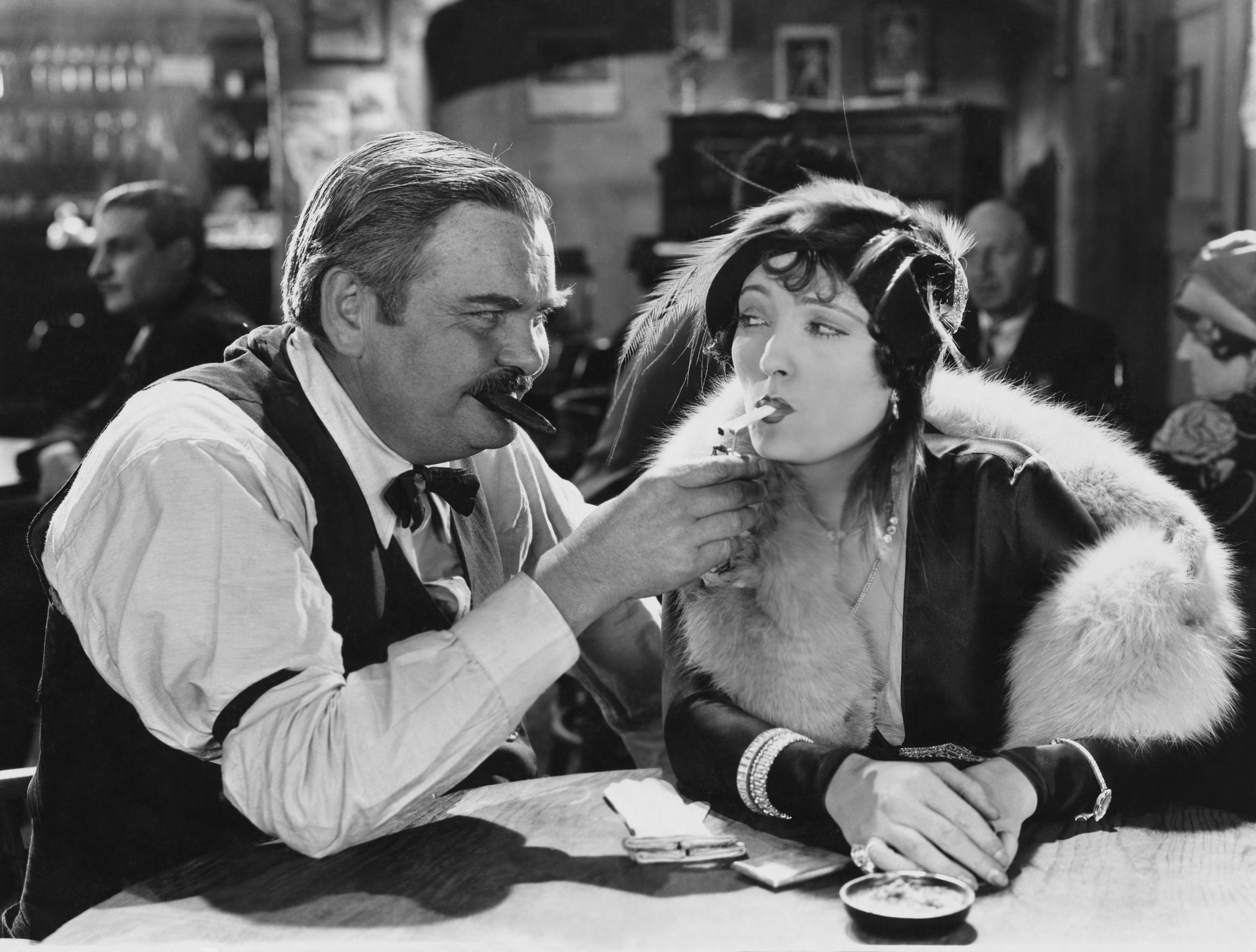 A black and white photo of a man and a woman in old fashioned clothes at a restaurant. The man is lighting the woman's cigarette.