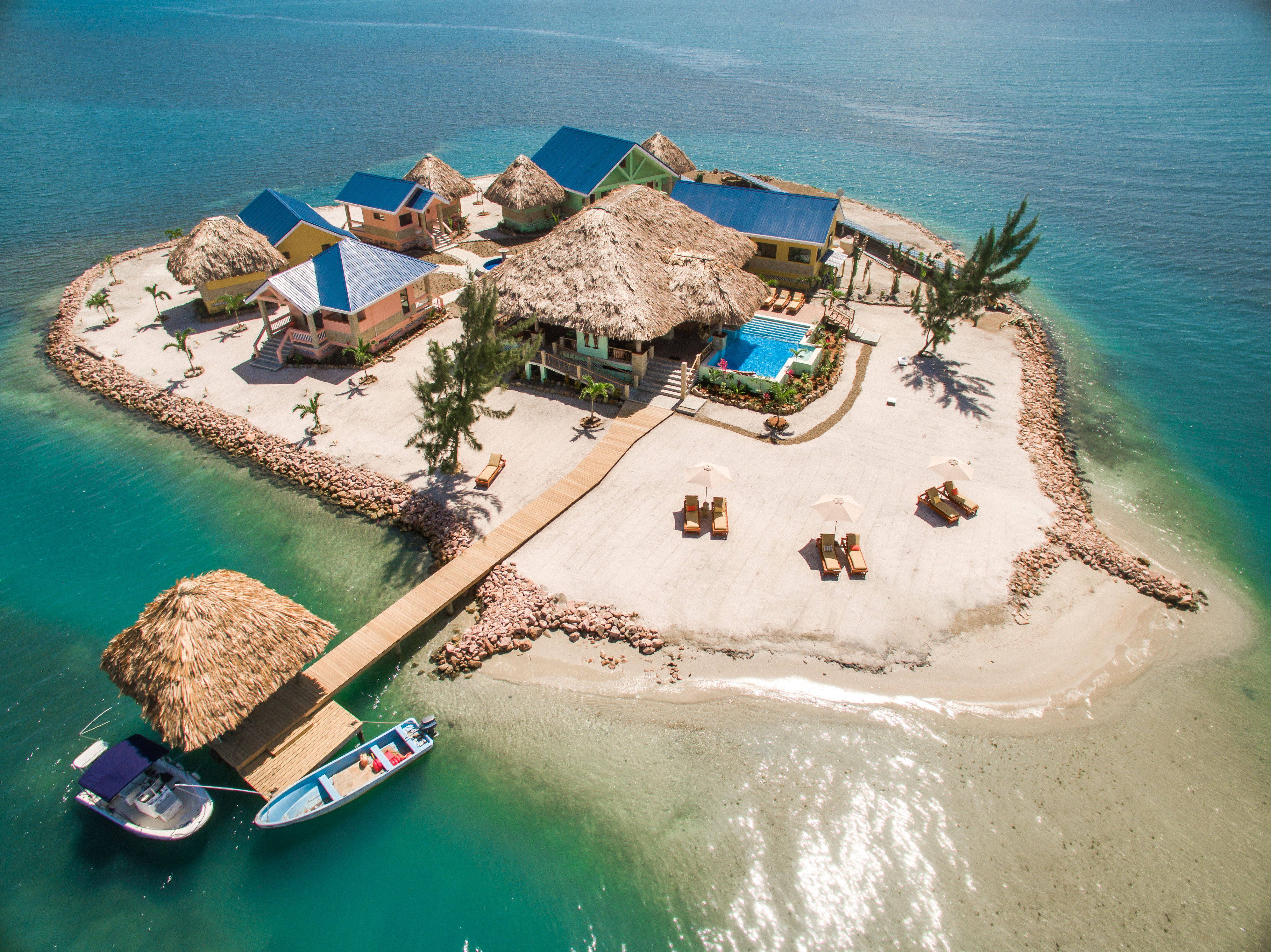An aerial view of a sandy island with a large thatched roof house surrounded by smaller homes with solar panels.
