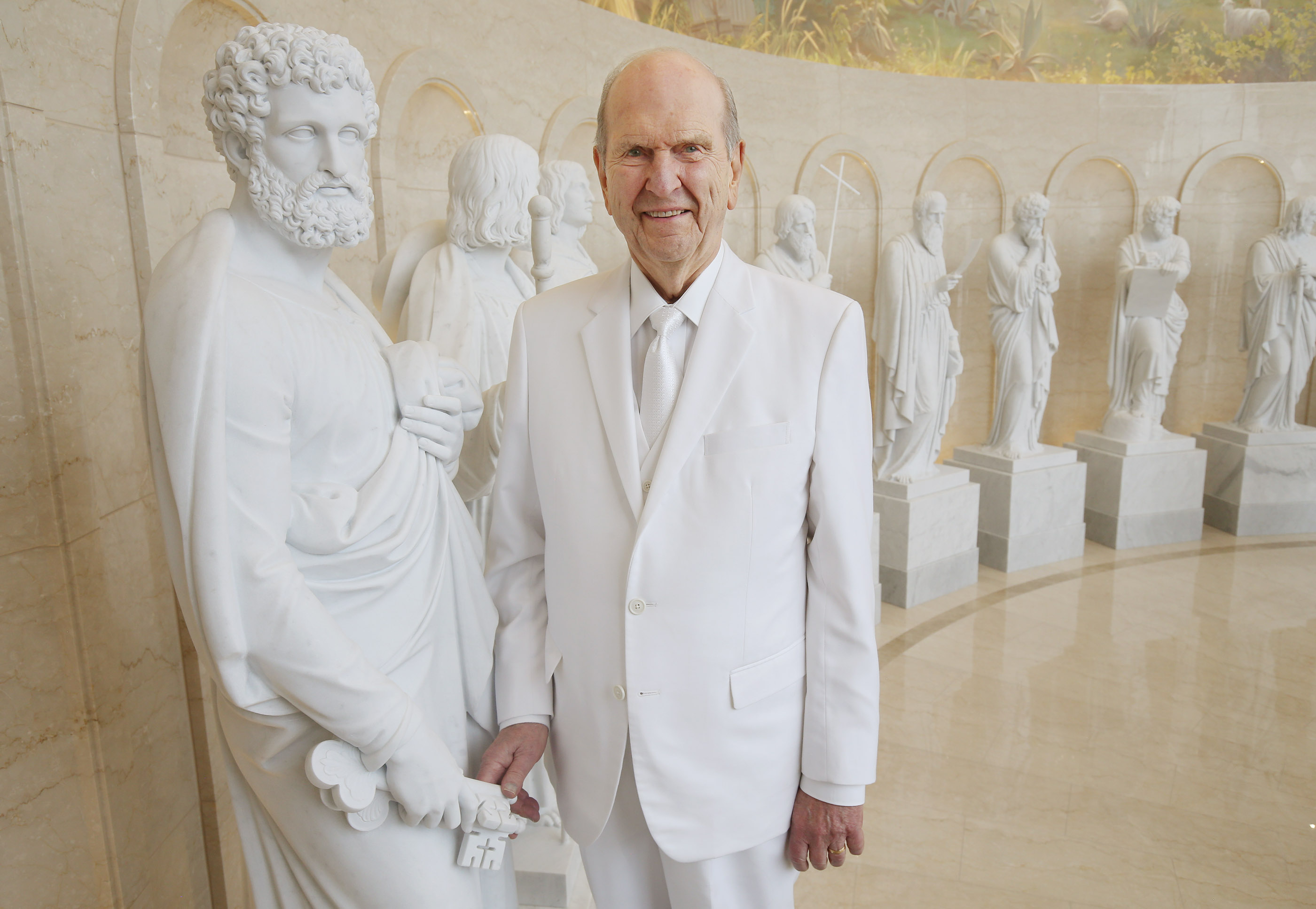 "Dressed in white temple clothing, President Russell M. Nelson stands in the Rome Italy Temple Visitors' Center next to a statue of Peter, by sculptor Bertel Thorvaldsen, in Rome, Italy, on Monday, March 11, 2019. The keys held in Peter's right hand are symbolic of Matthew 16:19, where Christ promises Peter, ""I will give unto thee the keys of the kingdom of heaven: and whatsoever thou shalt bind on earth shall be bound in heaven: and whatsoever thou shalt loose on earth shall be loosed in heaven."""