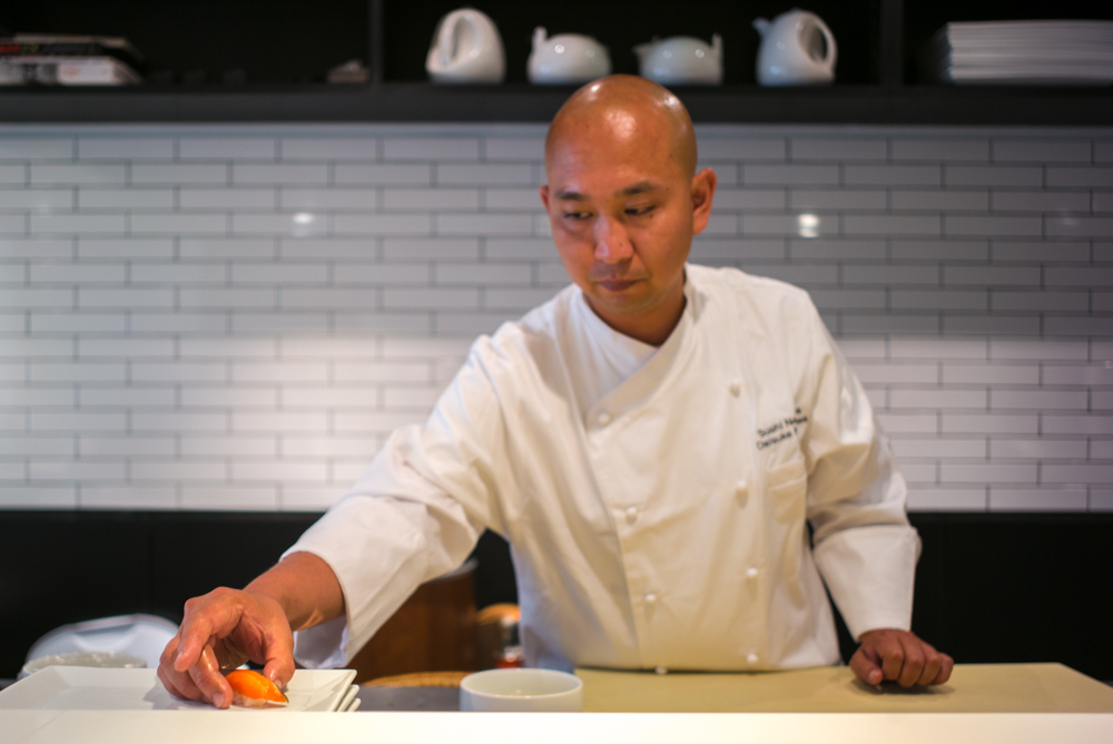 A sushi chef working behind the counter