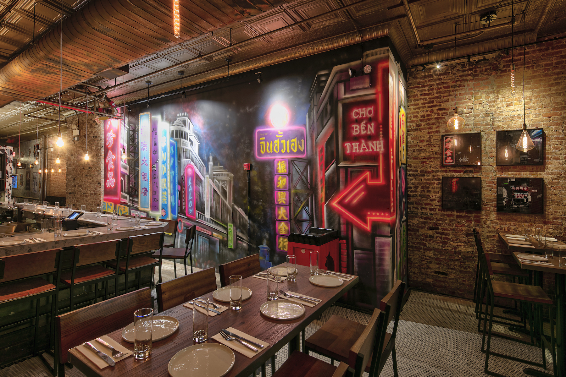 The interior of a restaurant with exposed brick walls, wooden tables placed closed together, and a mural depicting street food markets in Asia