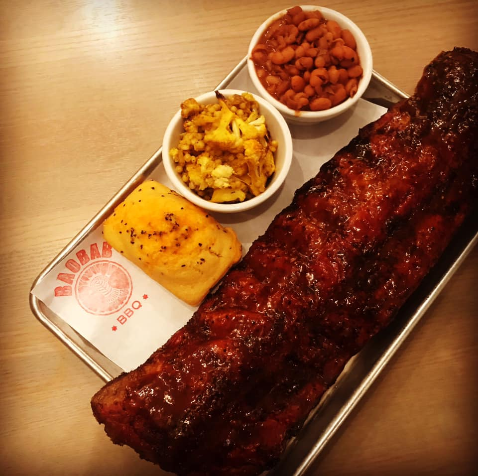 A slab of pork ribs with corn bread and sides on a metal tray.