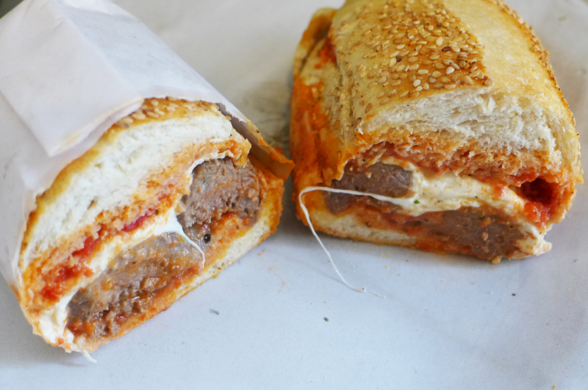 A meatball hero with red tomato sauce and white mozzarella is cut through the middle to reveal the interior.