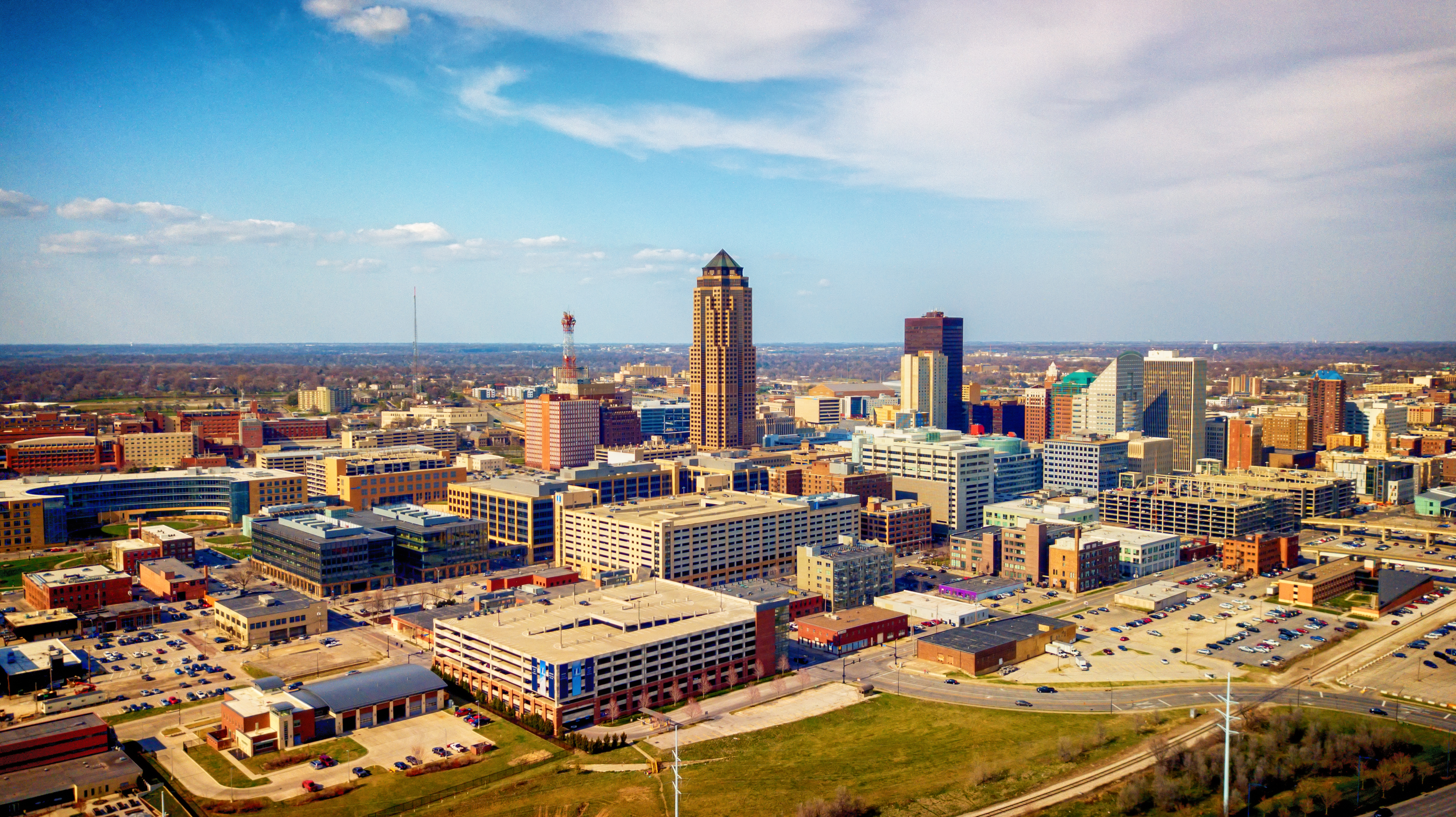 The colorful skyline of Des Moines, Iowa is seen in the foreground of farmland and a bright blue sky.