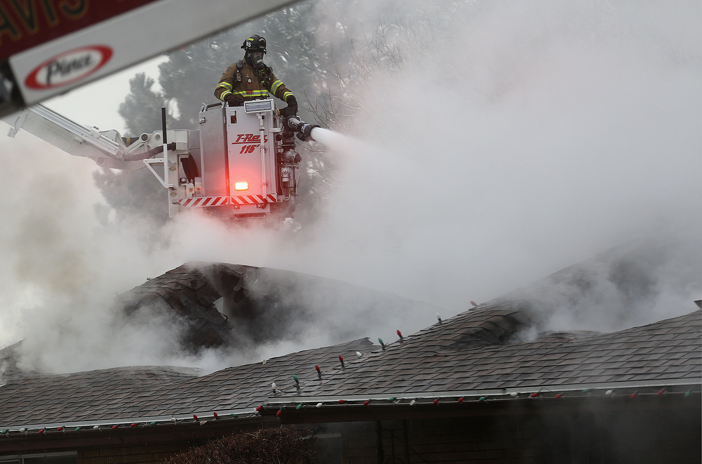 A firefighter battles a house fire in Bountiful on Tuesday, Jan. 14, 2020.