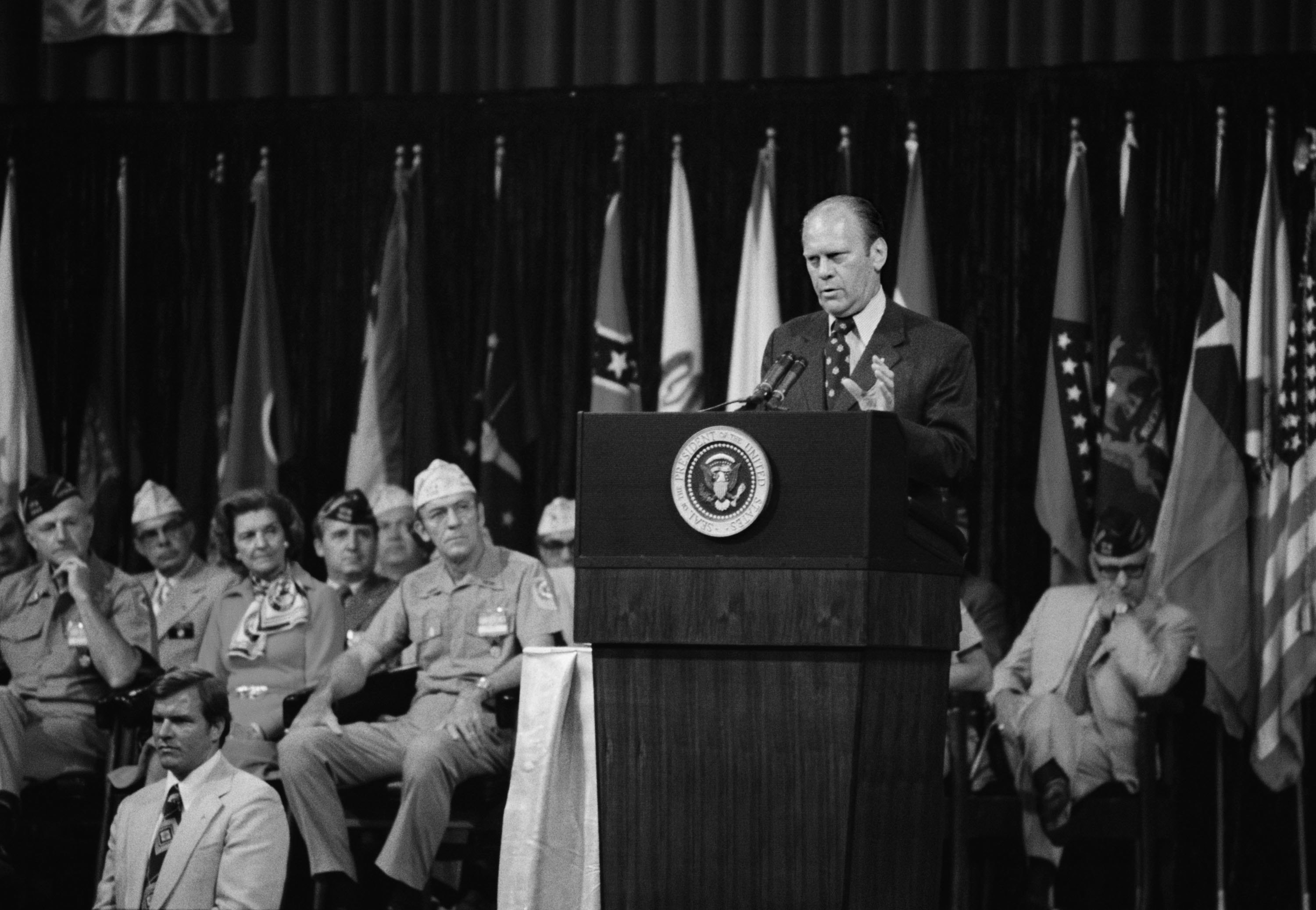President Gerald Ford speaking onstage at a podium with uniformed service members seated behind him, circa 1974.