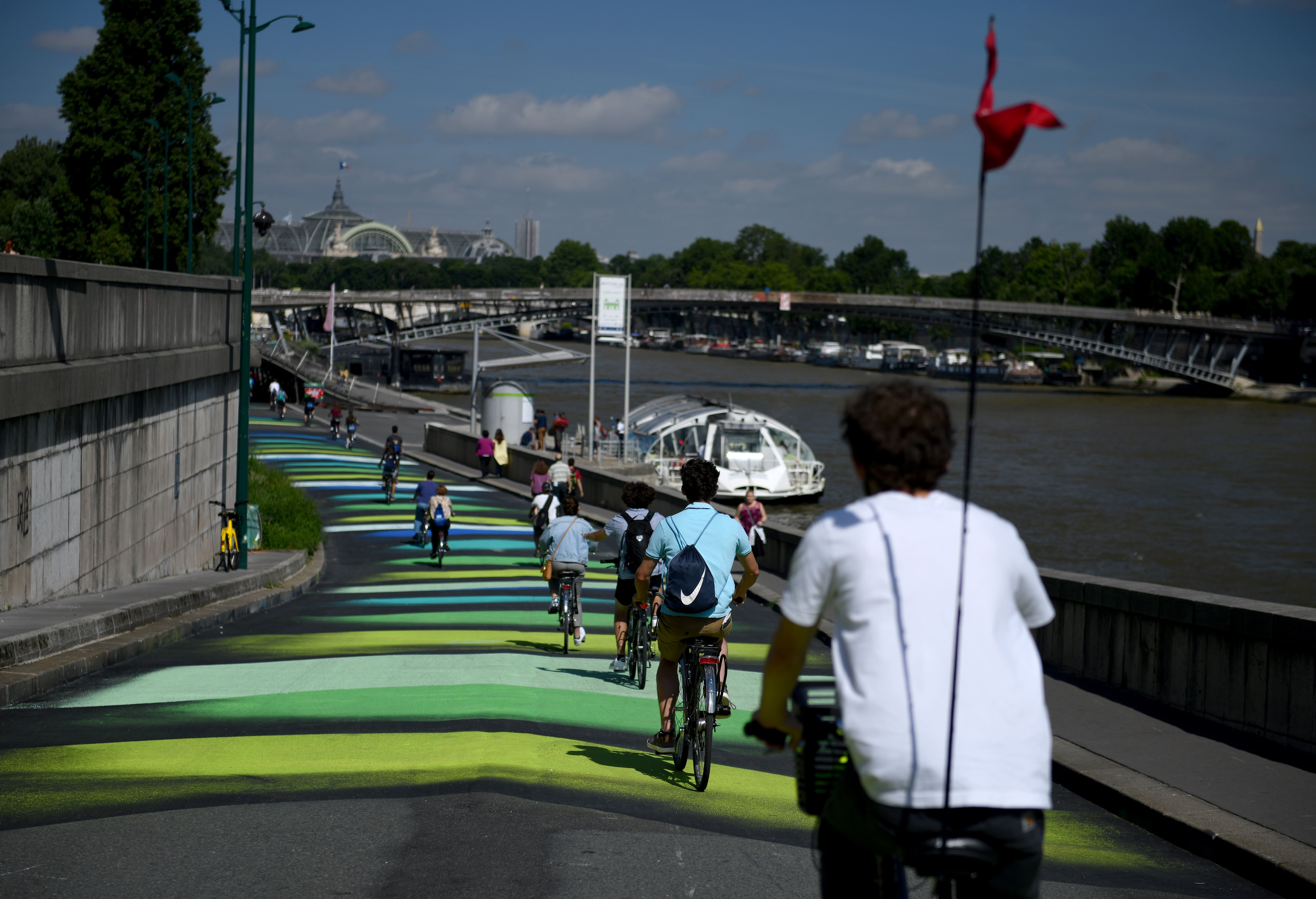 A crowd of cyclists ride down a colored bike path on the bank of the River Seine in Paris.
