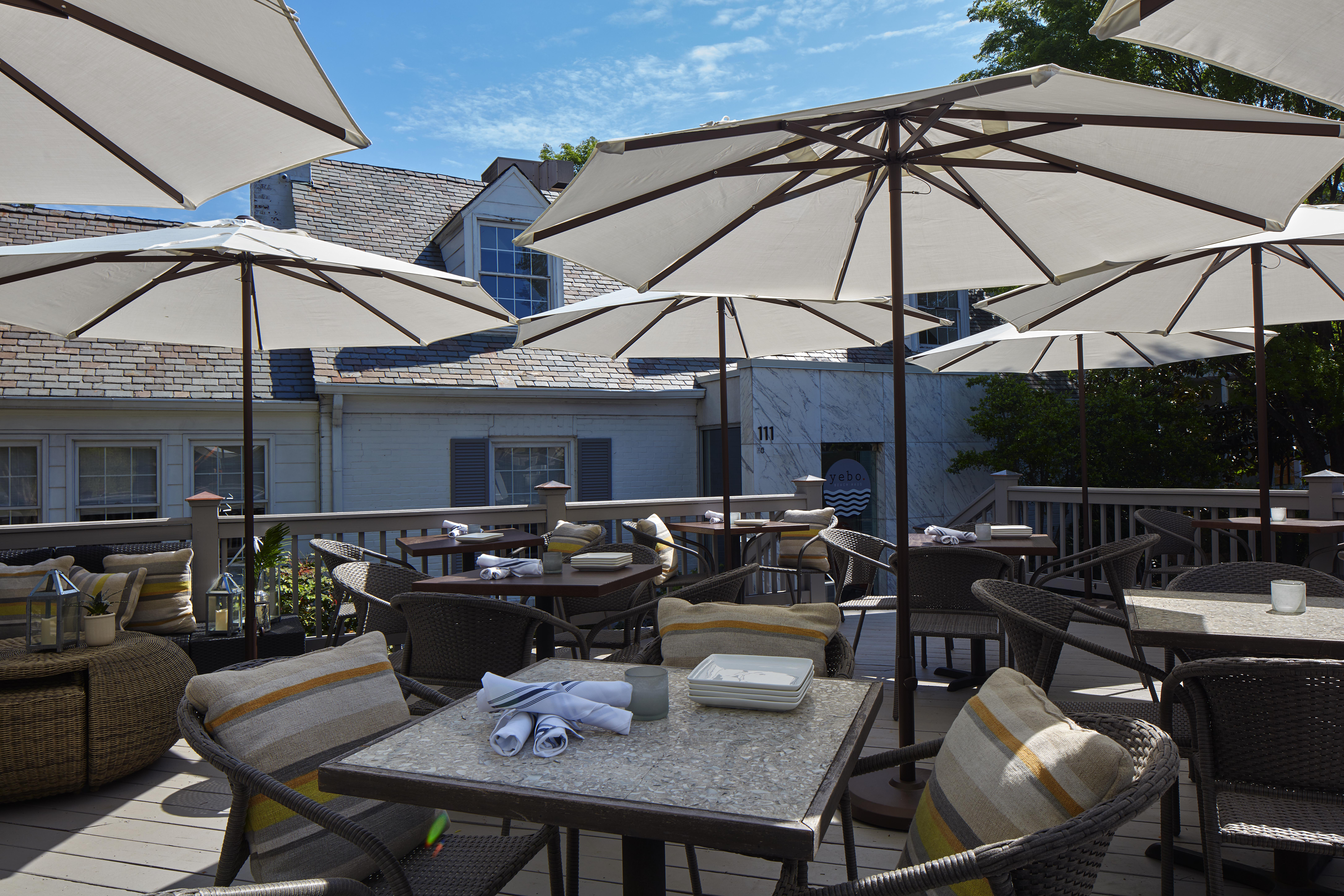 The outdoor patio at the current location of Yebo Beach Haus with tables and umbrellas