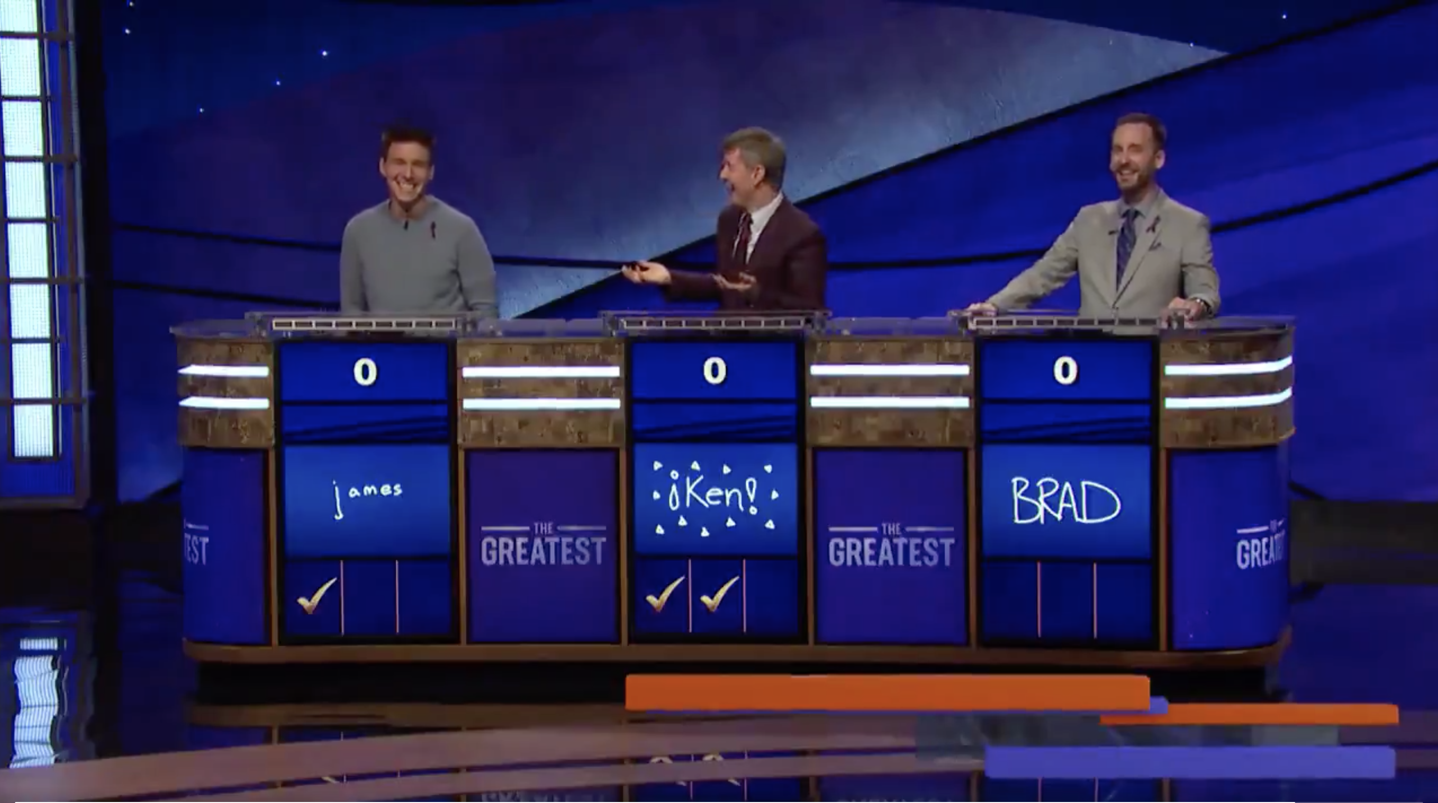 Screenshot from the final episode of 'Jeopardy! Greatest of All Time' showing James Holzhauer, Ken Jennings and Brad Rutter reacting with amusement after Holzhauer taunted Rutter.