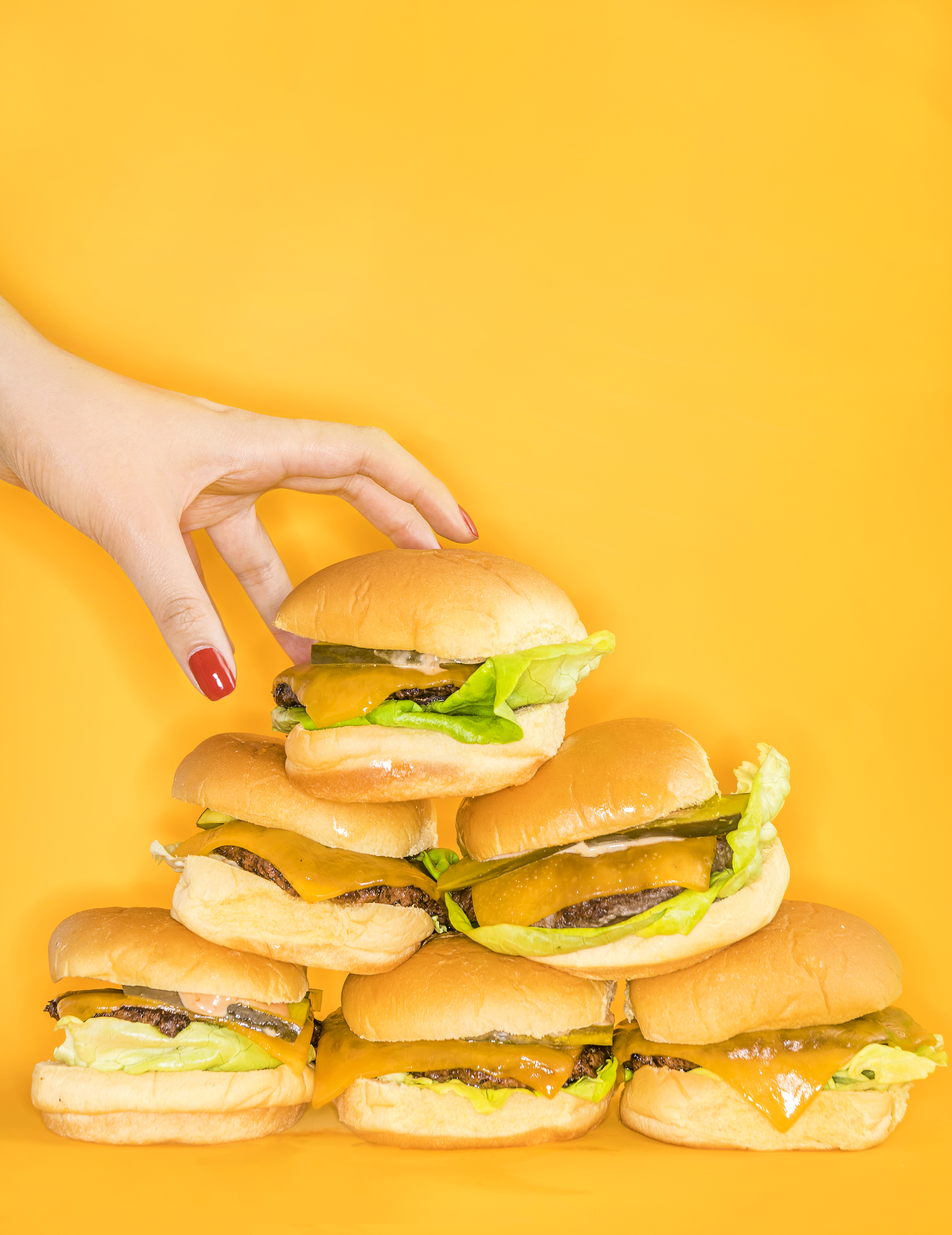 A woman's red-manicured hand reaches for a pile of cheeseburgers on a yellow background.