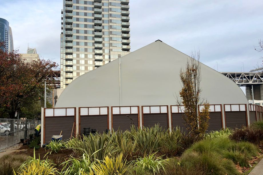 A large white tent structure with a corrugated fence around it.