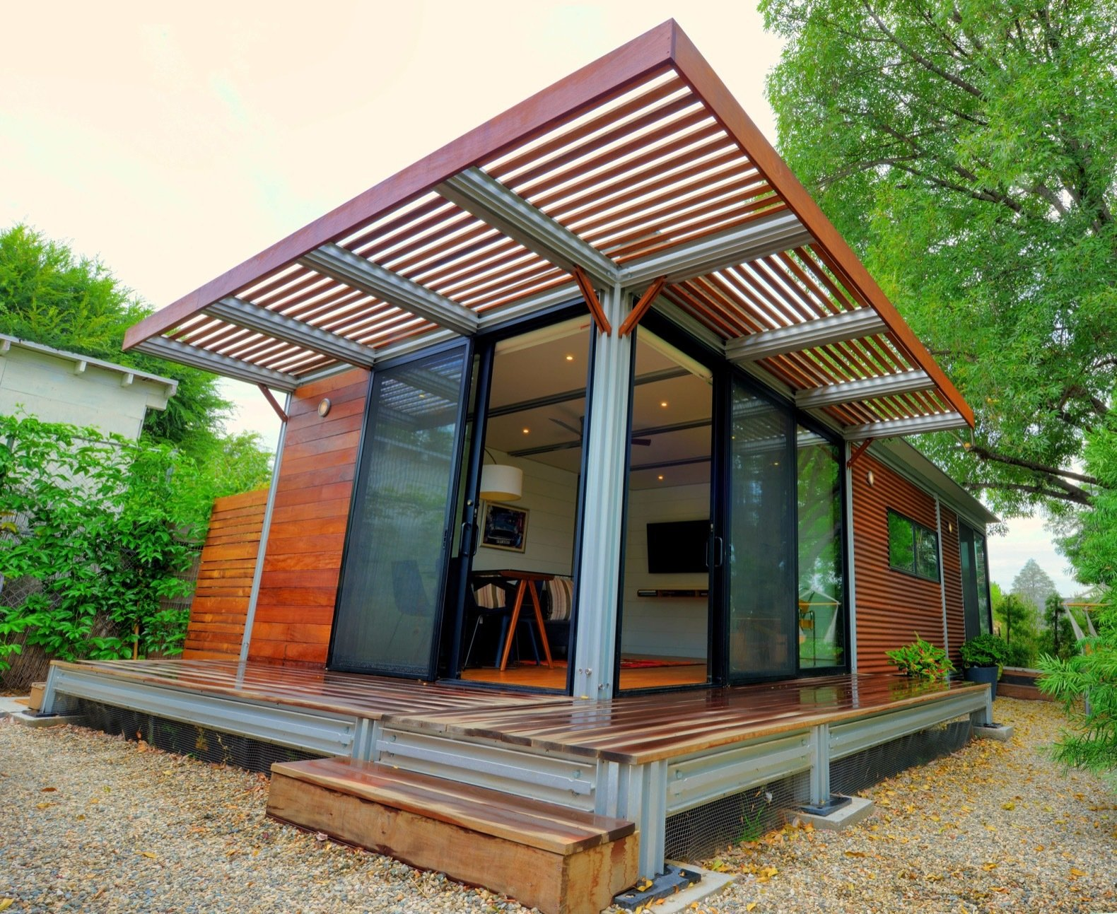 Boxy home with partially covered porch and sliding glass doors.