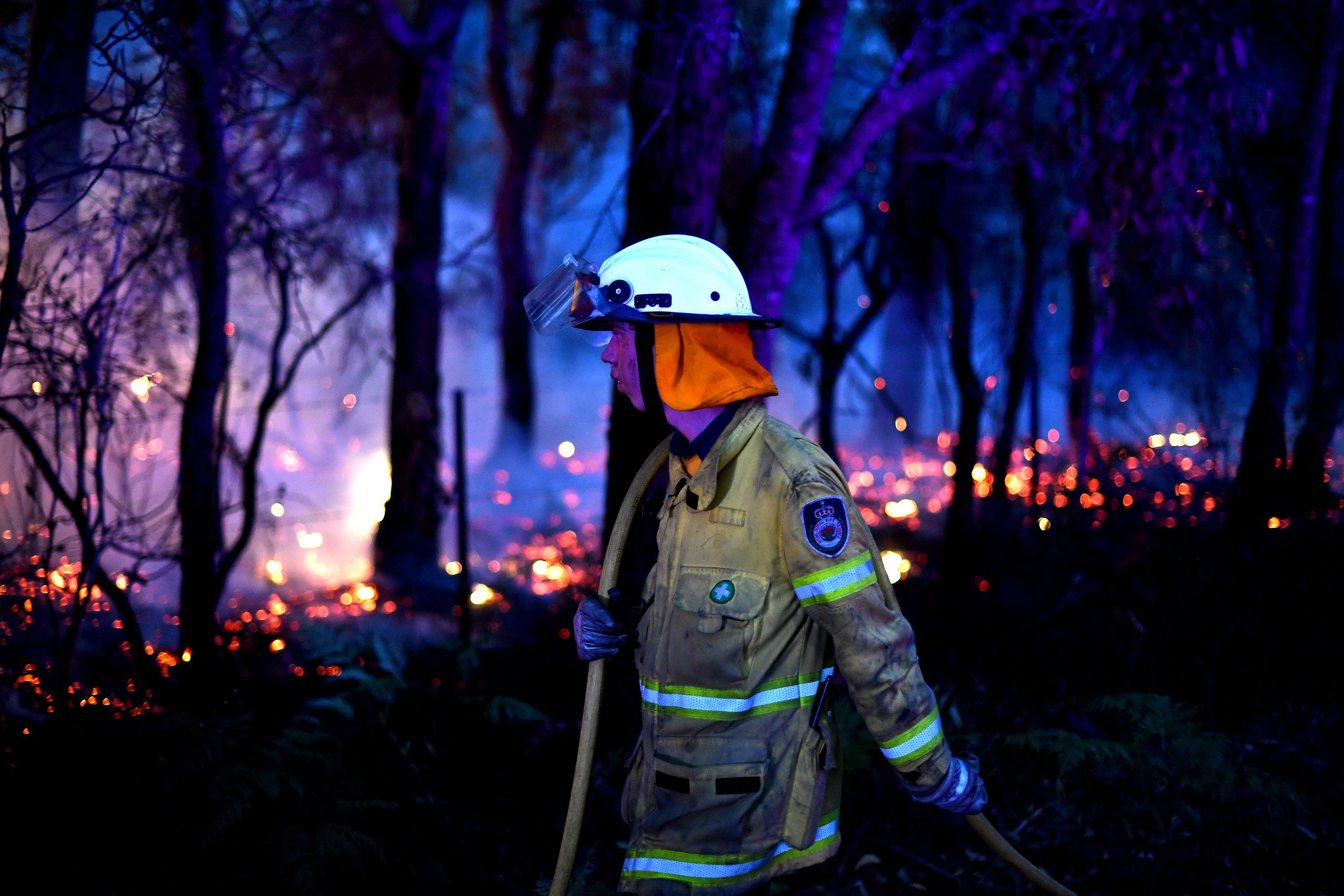 This photo taken on December 7, 2019 shows a firefighter conducting back burning measures to secure residential areas from encroaching bushfires at the Mangrove area, some 90-110 kilometres north of Sydney.