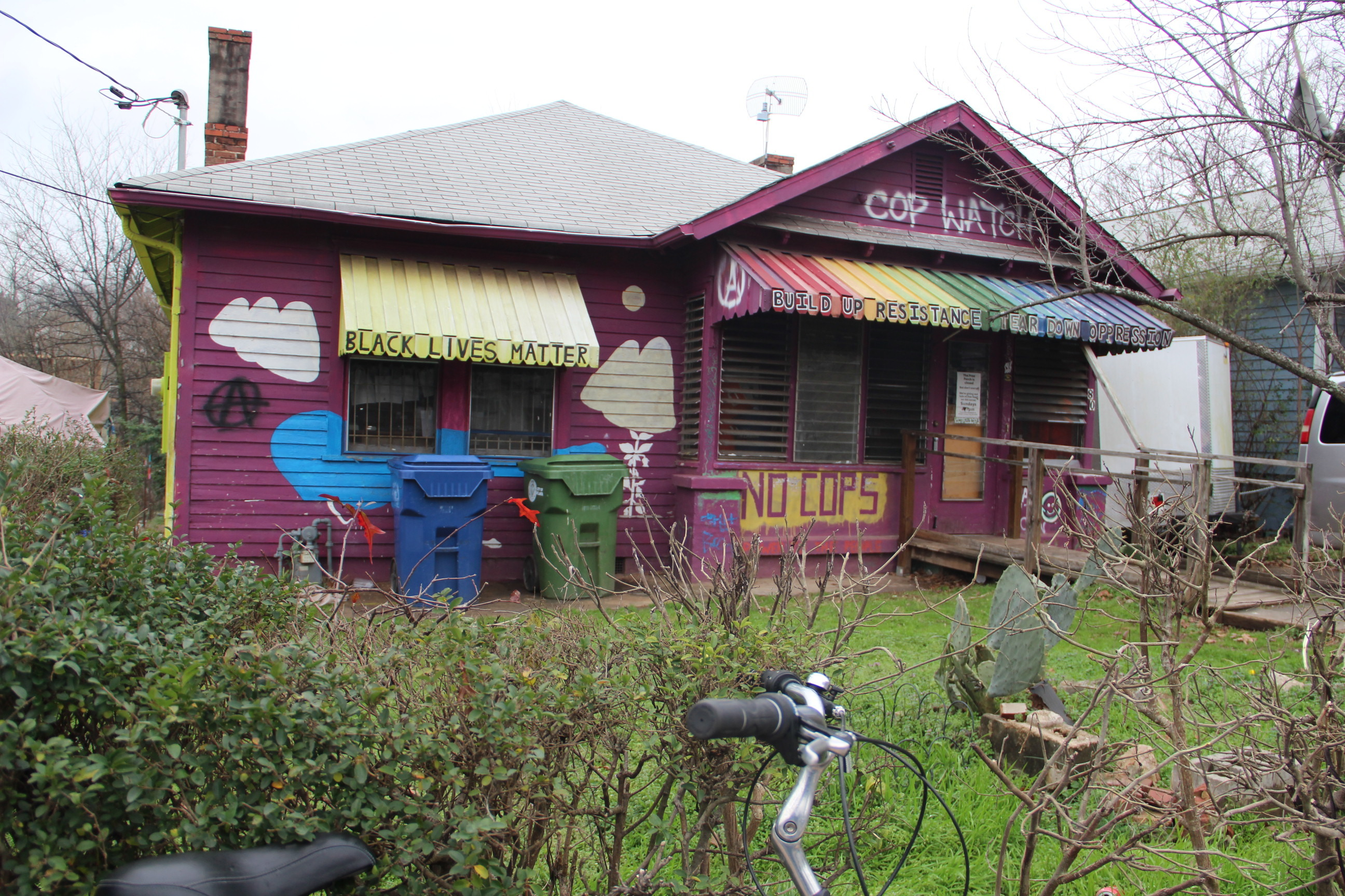 A purple bungalow painted with yellow and rainbow awnings.