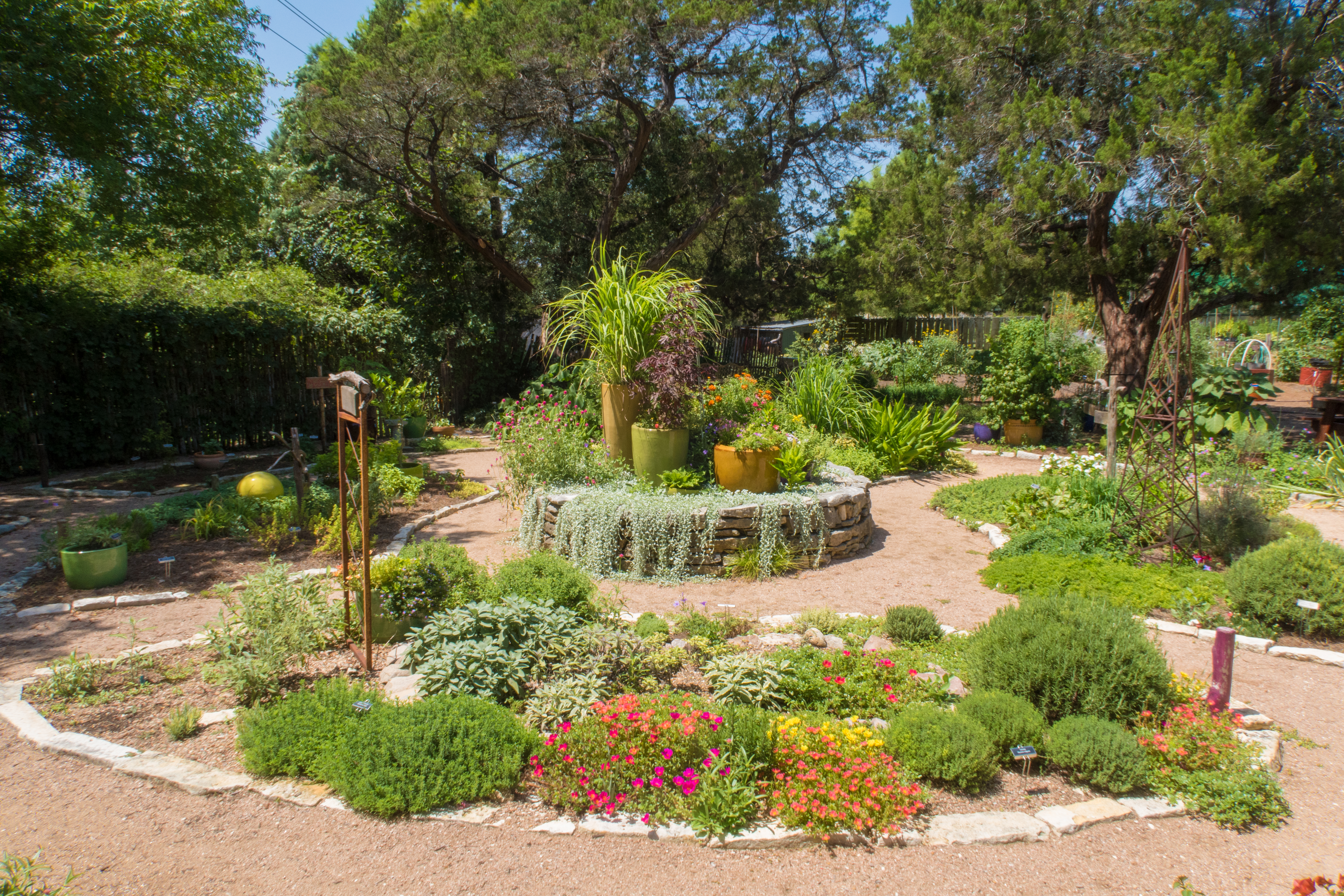 A semi-formal garden with wide, curving paths of decomposed granite circular planting beds—raised and ground-level—full of blooming plants with a variety of shapes and textures. Large leafy trees are in the background.