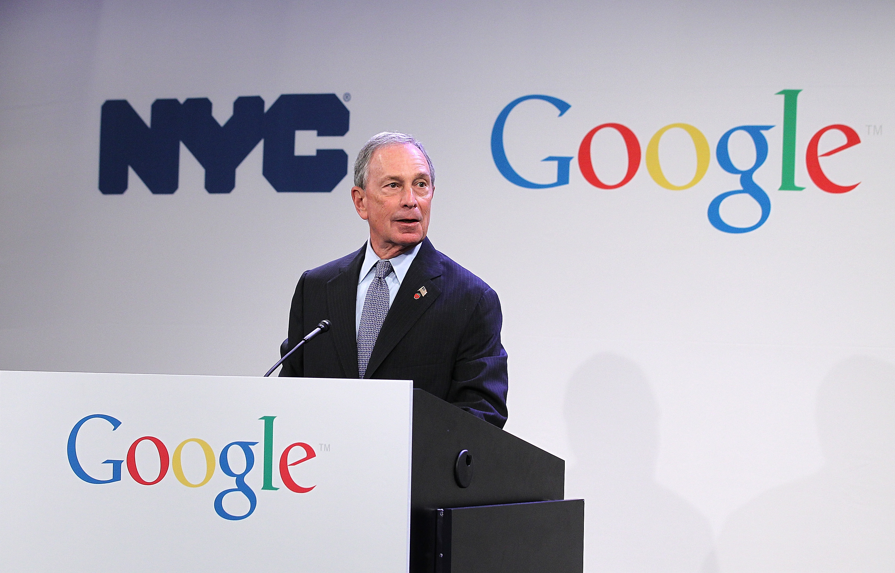 "Mike Bloomberg appears on a podium that says ""Google"" on it."