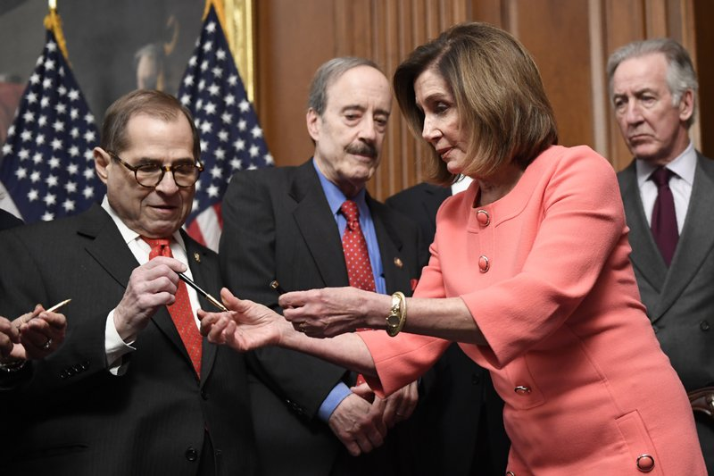 House Speaker Nancy Pelosi of Calif., second from right, gives pens to, from left, House Judiciary Committee Chairman Rep. Jerrold Nadler, D-N.Y., House Foreign Affairs Committee Chairman Rep. Eliot Engel, D-N.Y., and House Ways and Means Committee Chairman Rep. Richard Neal, D-Mass., after she signed the resolution to transmit the two articles of impeachment against President Donald Trump to the Senate for trial on Capitol Hill in Washington, Wednesday, Jan. 15, 2020.