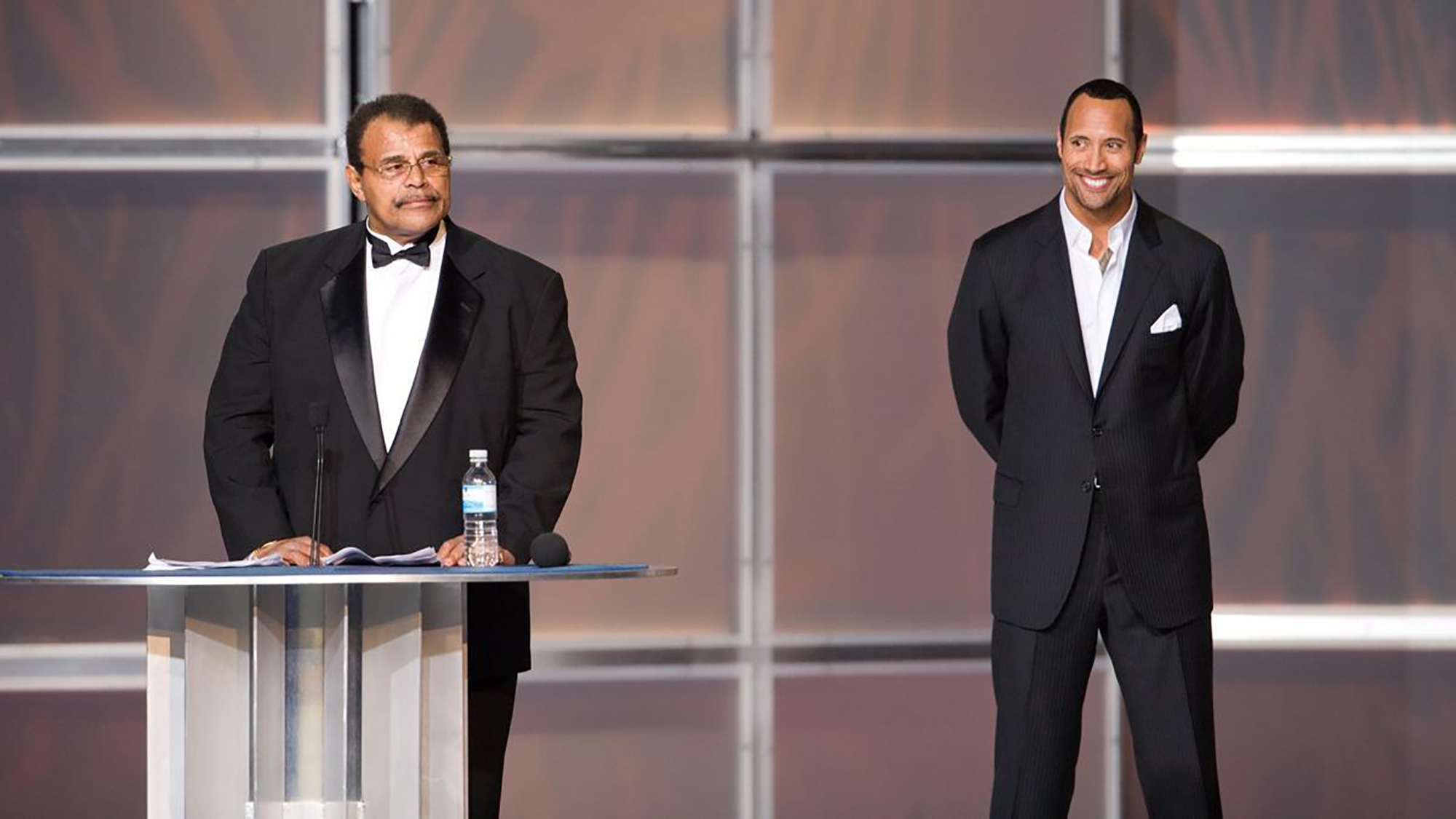 """In this 2008 photo provided by WWE, Inc., Rocky """"Soul Man"""" Johnson, left, speaks at his WWE Hall of Fame induction ceremony, as his son, Dwayne """"The Rock"""" Johnson watches."""