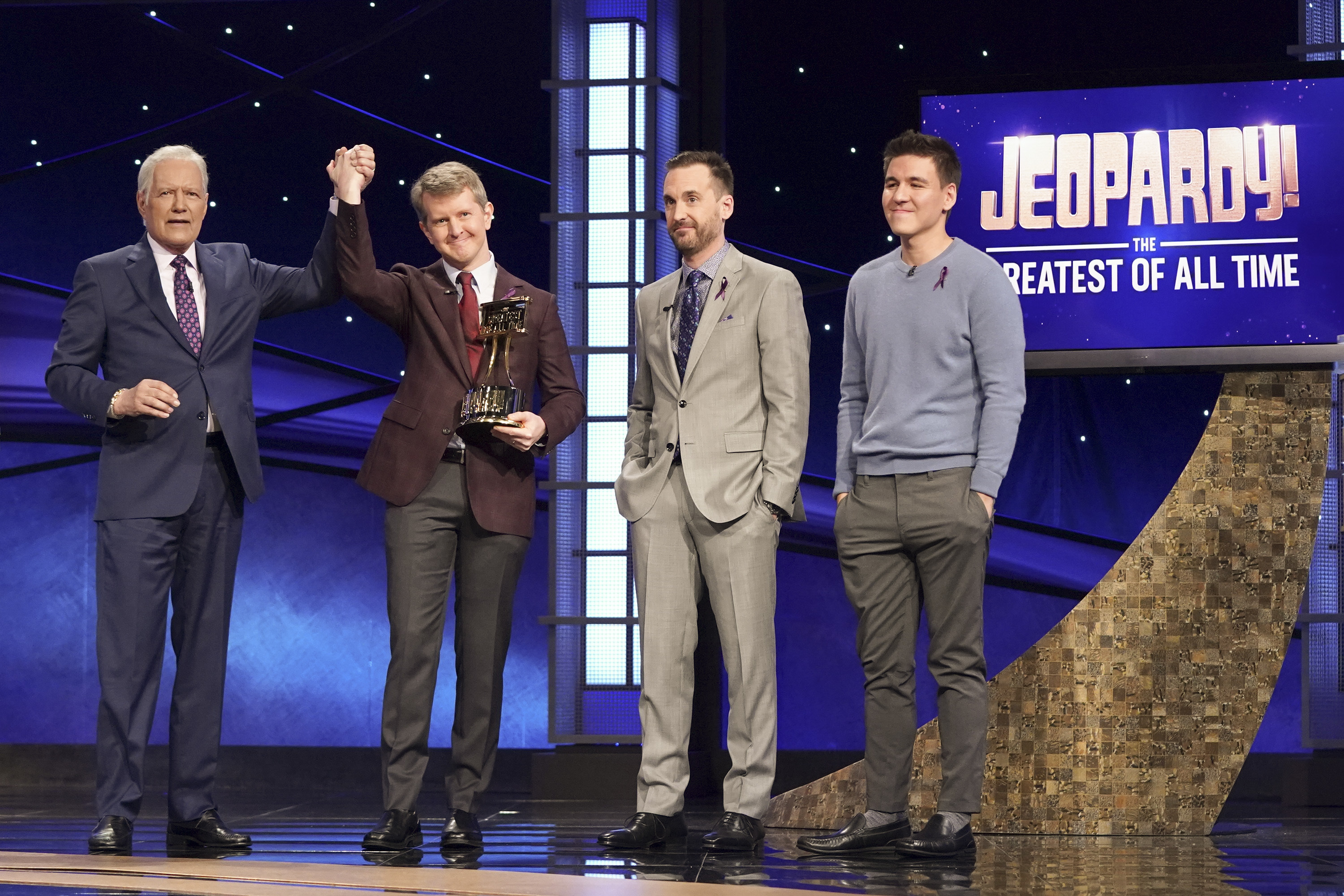 "Alex Trebek joins hands with contestant Ken Jennings after he won ""JEOPARDY! The Greatest of All Time,"" as fellow contestants Brad Rutter and James Holzhauer look on."