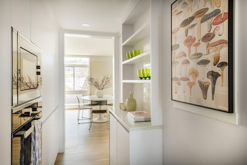 A narrow modern kitchen with appliances and cabinetry built into the walls.