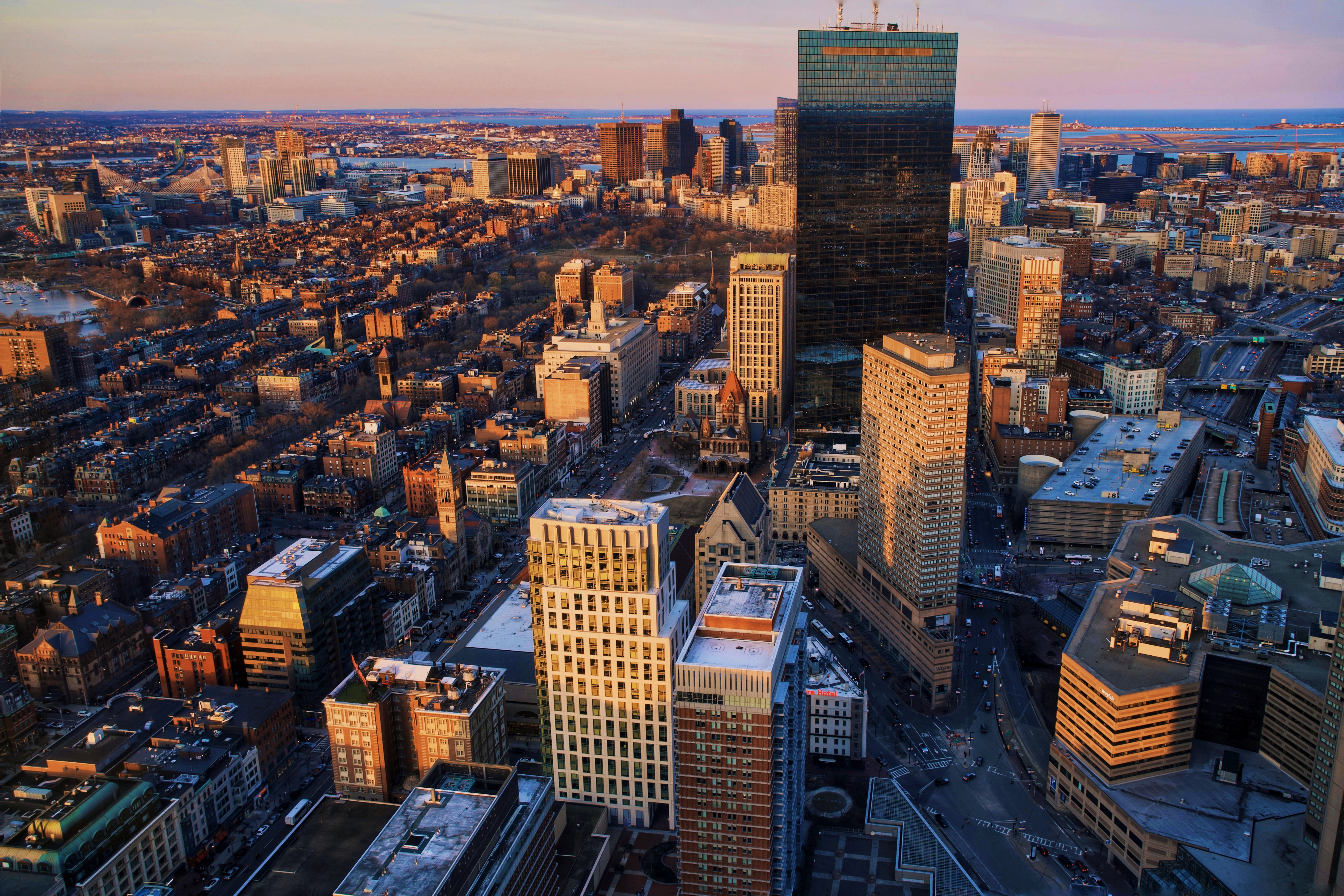An aerial shot of the Boston skyline and the region beyond at sunset.