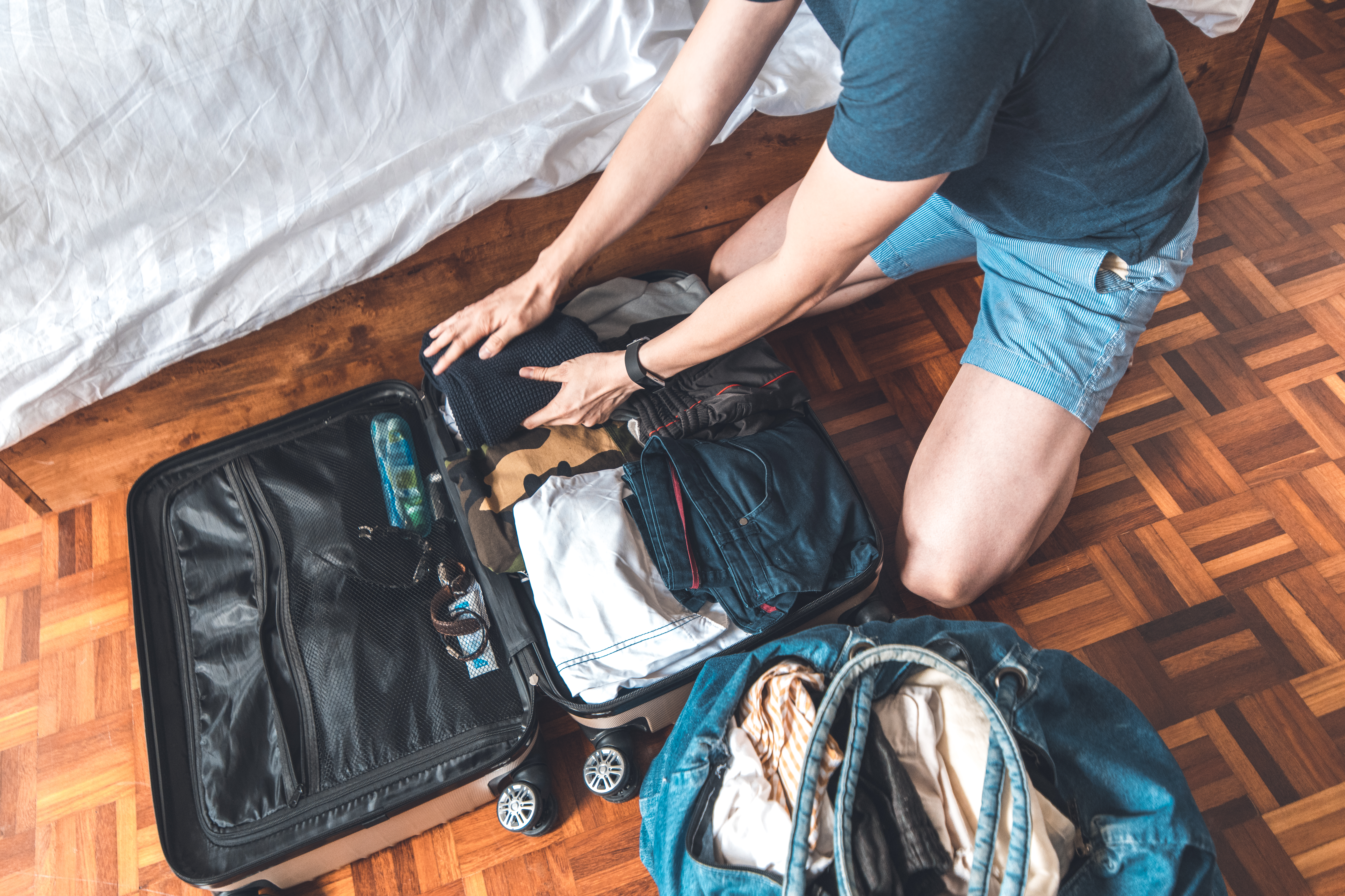 A man kneels on a hardwood floor with a duffel bag at his side, packing a suitcase.