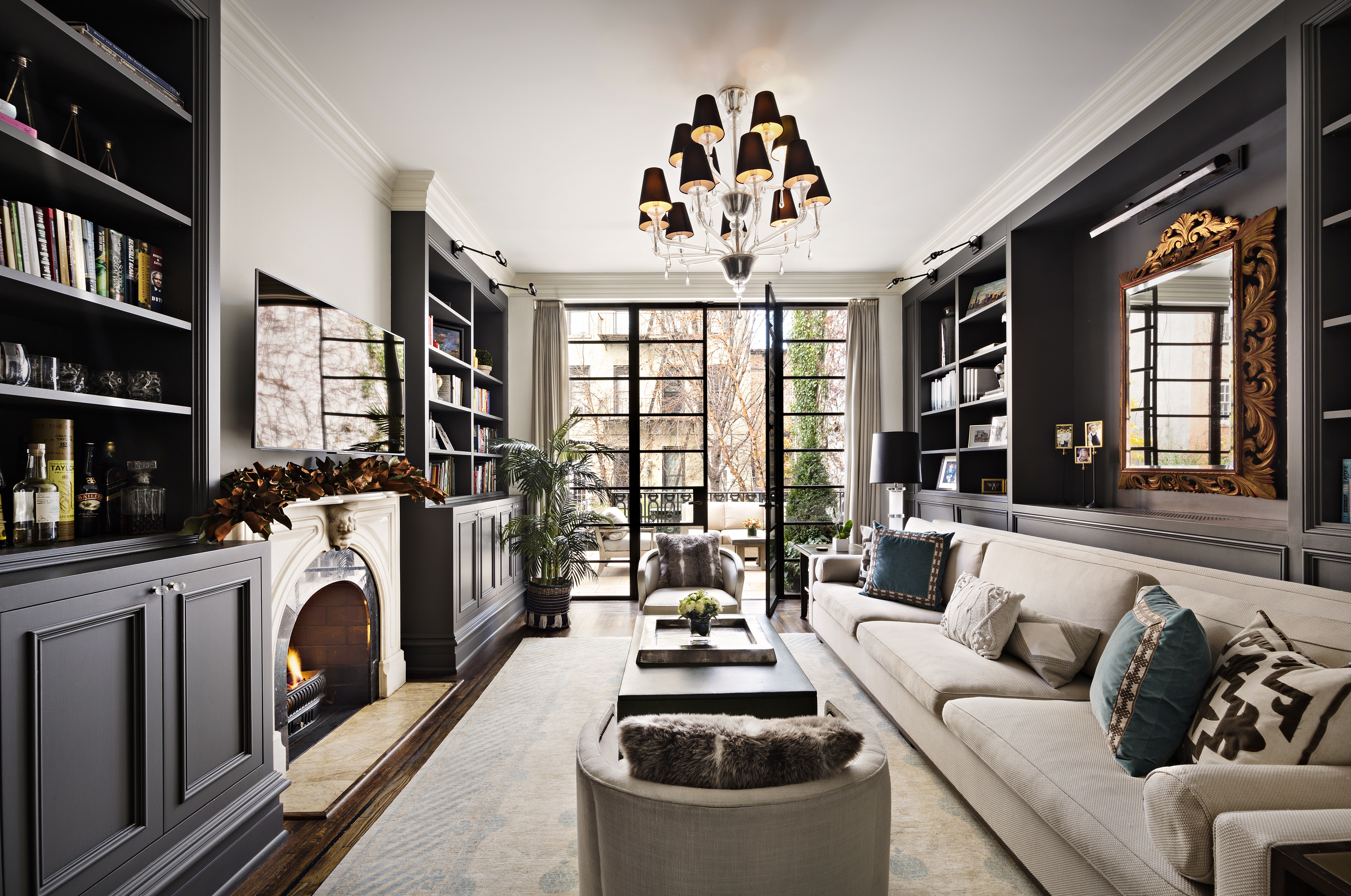 A living room area with a fireplace, a beige couch, a chandelier, floor-to-ceiling glass casement doors, and wooden bookshelves.