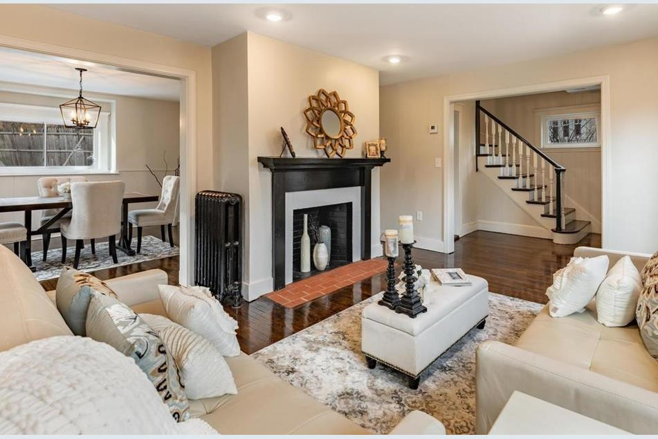 A living room with furniture facing a fireplace, and there are stairs visible from the hallway just beyond.